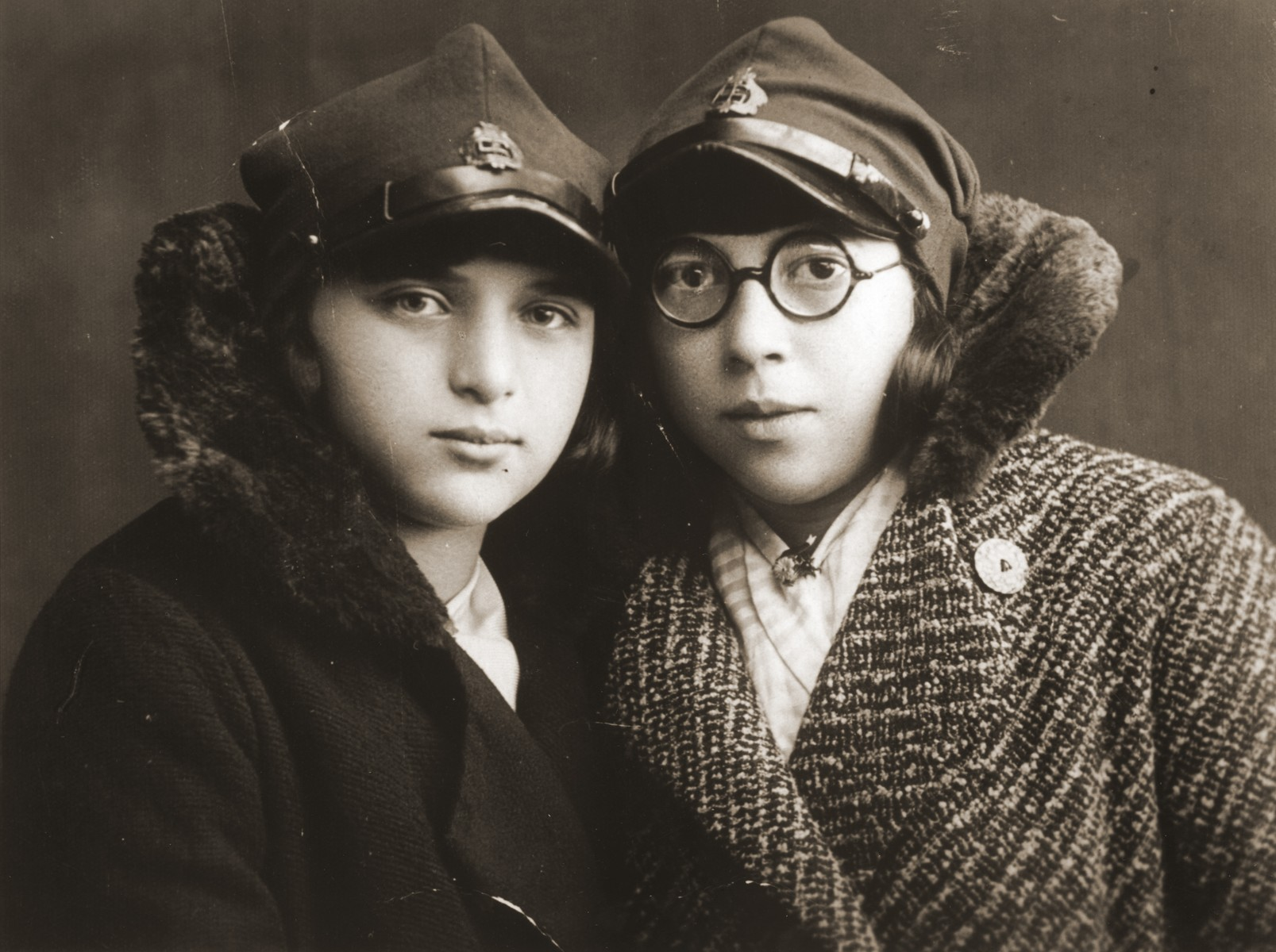 Felicja Berland poses with her friend Genia Laks wearing the hats of their school uniform.