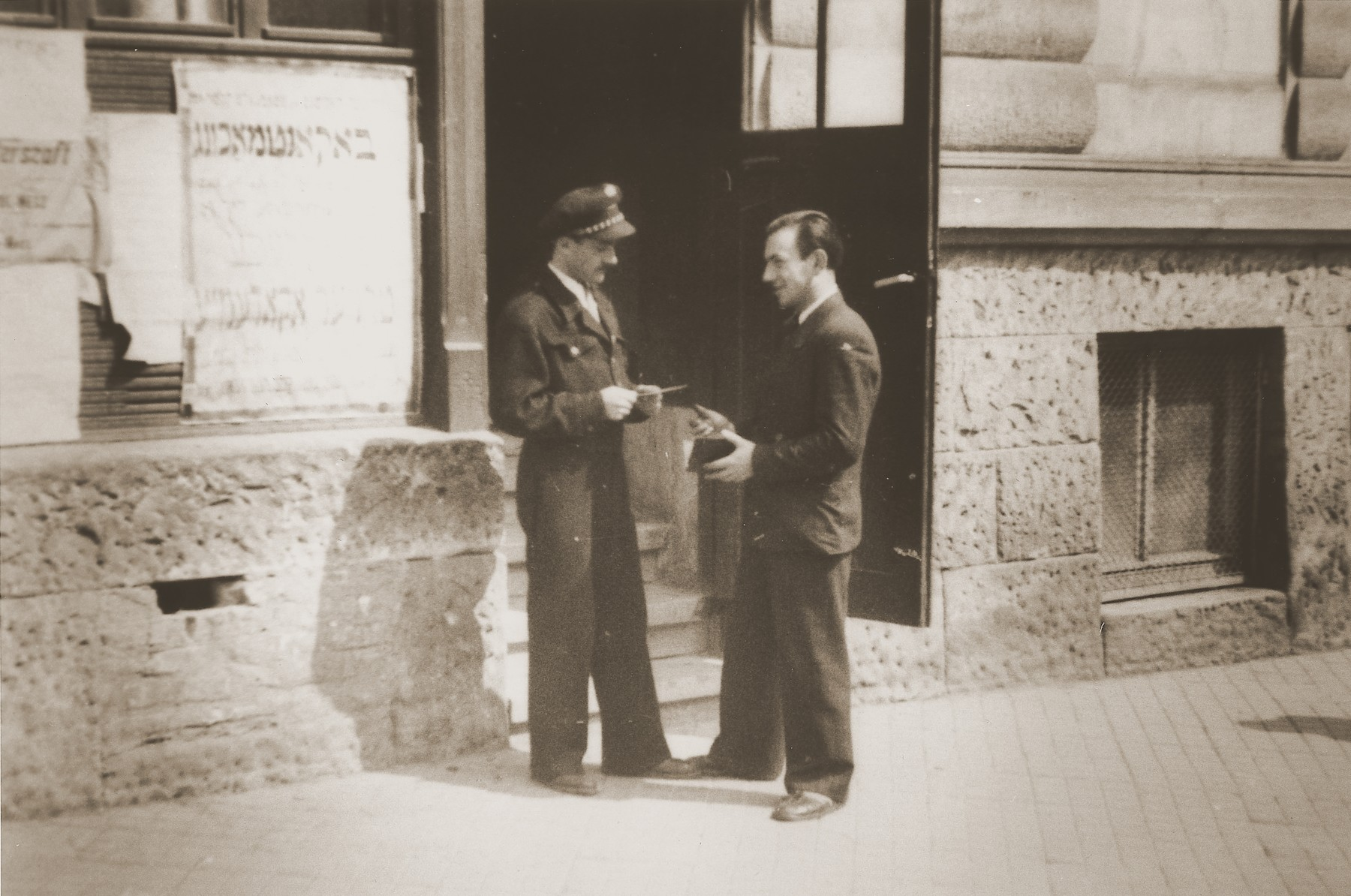 "Police officer M. Ritter checks the papers of a camp resident at the entrance to a building in the Stuttgart DP camp.  One image from the Stuttgart Jewish DP camp album entitled, ""Jidiszer D.P. Center UNRRA--P.C.IRO in Stuttgart,"" compiled and photographed by Alexander Fiedel and dedicated to Moses Kornberg, head of the commissary."