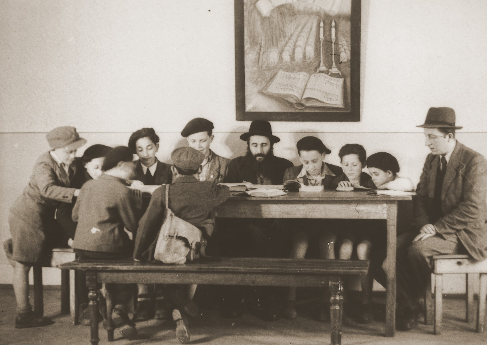 """A rabbi teaches a group of boys in a cheder [religious elementary school] in the Stuttgart DP camp.  To right of rabbi is Lova Warszaczyk.  Next to him is Binstock  One image from the Stuttgart Jewish DP camp album entitled, """"Jidiszer D.P. Center UNRRA--P.C.IRO in Stuttgart,"""" compiled and photographed by Alexander Fiedel and dedicated to Moses Kornberg, head of the commissary."""