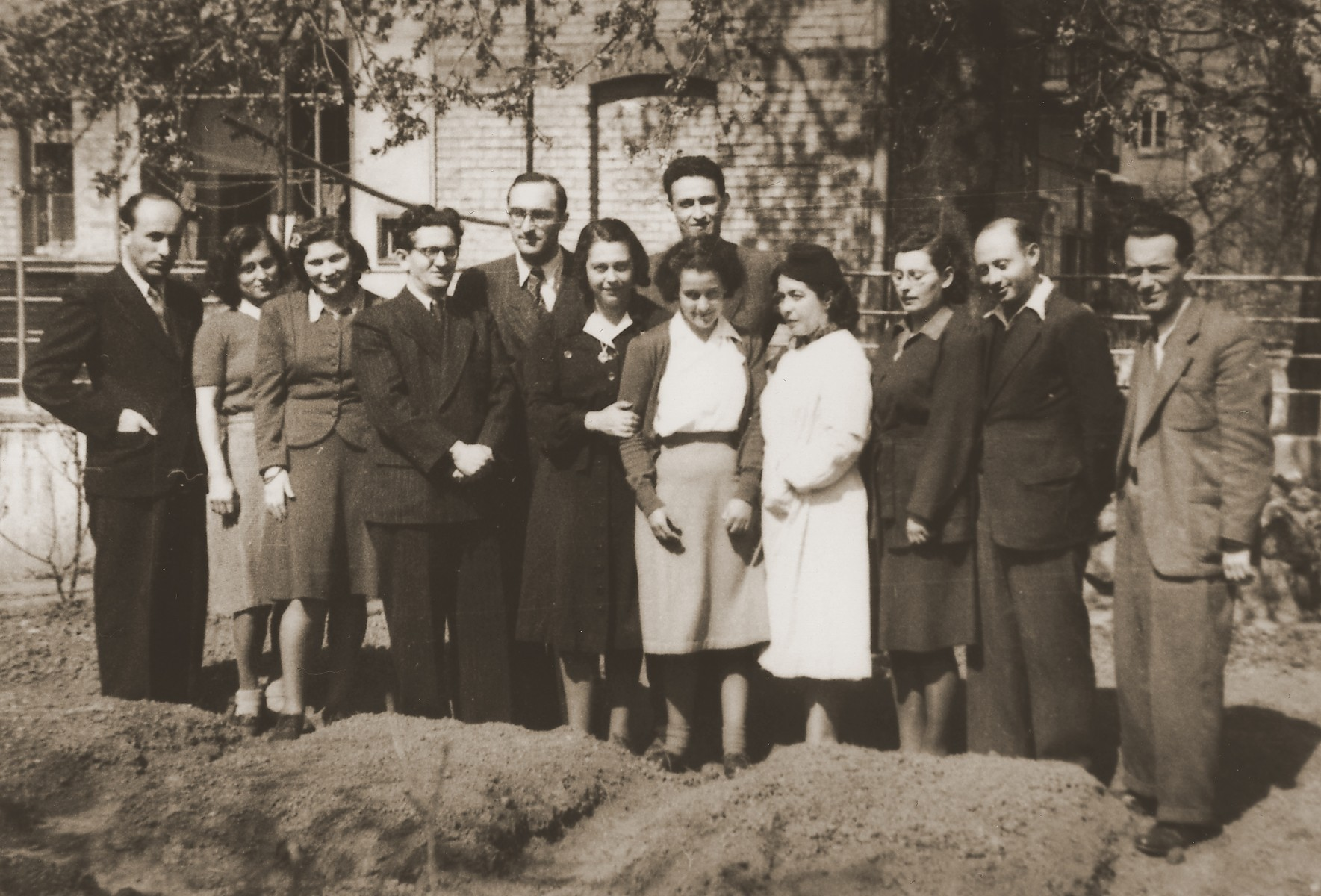 """Group portrait of the teaching staff at the school in the Stuttgart DP camp.  One image from the Stuttgart Jewish DP camp album entitled, """"Jidiszer D.P. Center UNRRA--P.C.IRO in Stuttgart,"""" compiled and photographed by Alexander Fiedel and dedicated to Moses Kornberg, head of the commissary.  Among those pictured is (?) Levi first on the left; Wolf Gassenbauer, fourth from the left; (?) Scherer, fifth from the left; and (?) Richtman, on the right."""