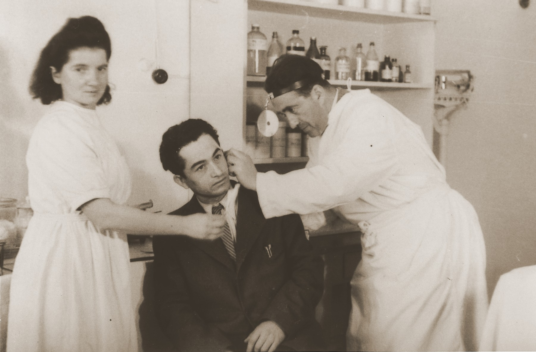 "Dr. J. Weitz examines the ear of a young man at the clinic in the Stuttgart DP camp.  One image from the Stuttgart Jewish DP camp album entitled, ""Jidiszer D.P. Center UNRRA--P.C.IRO in Stuttgart,"" compiled and photographed by Alexander Fiedel and dedicated to Moses Kornberg, head of the commissary."