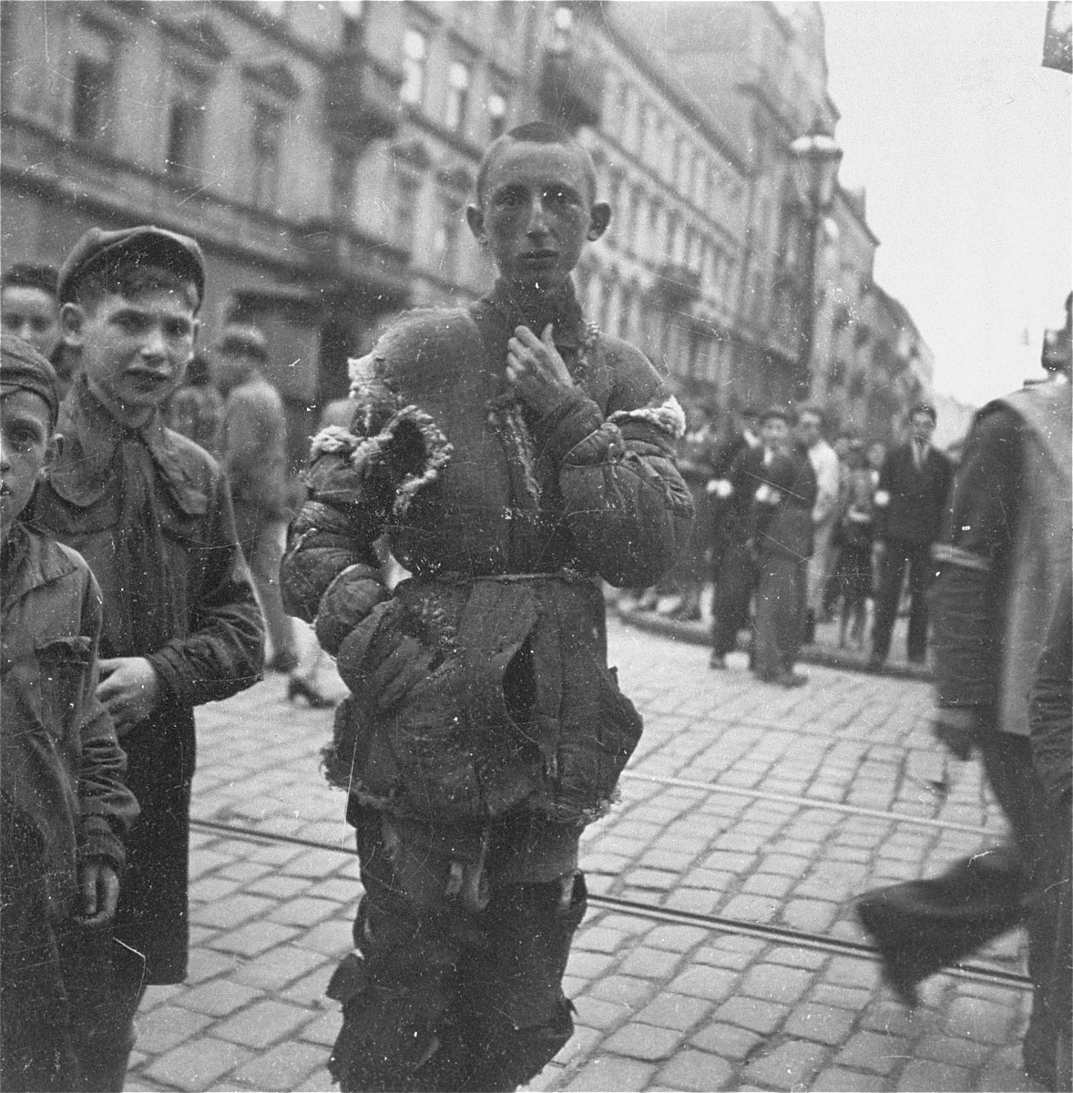"A destitute youth in the Warsaw ghetto.    Joest's original caption reads: ""This youth had a jacket made entirely out of scraps that were stitched together and which had again split in many places.  He had it good in comparison with those children in thin jackets who were not wearing even one shoe."""