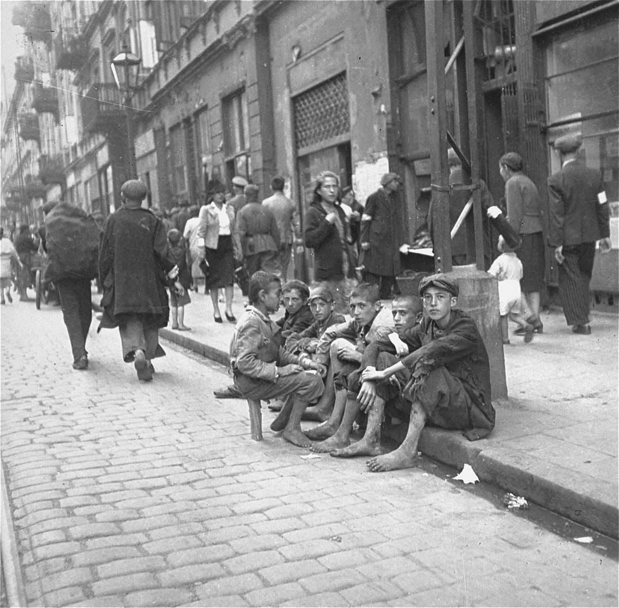 "A group of destitute boys on a curb in the Warsaw ghetto.    Joest's original caption reads: ""It was striking to me how many youngsters did not wear shoes.  It was already cold on this day.  In the background of my photo I discovered later this Wehrmacht sergeant with his companion, a soldier.  I thought to myself that he was going shopping in the ghetto, perhaps for jewelry."""