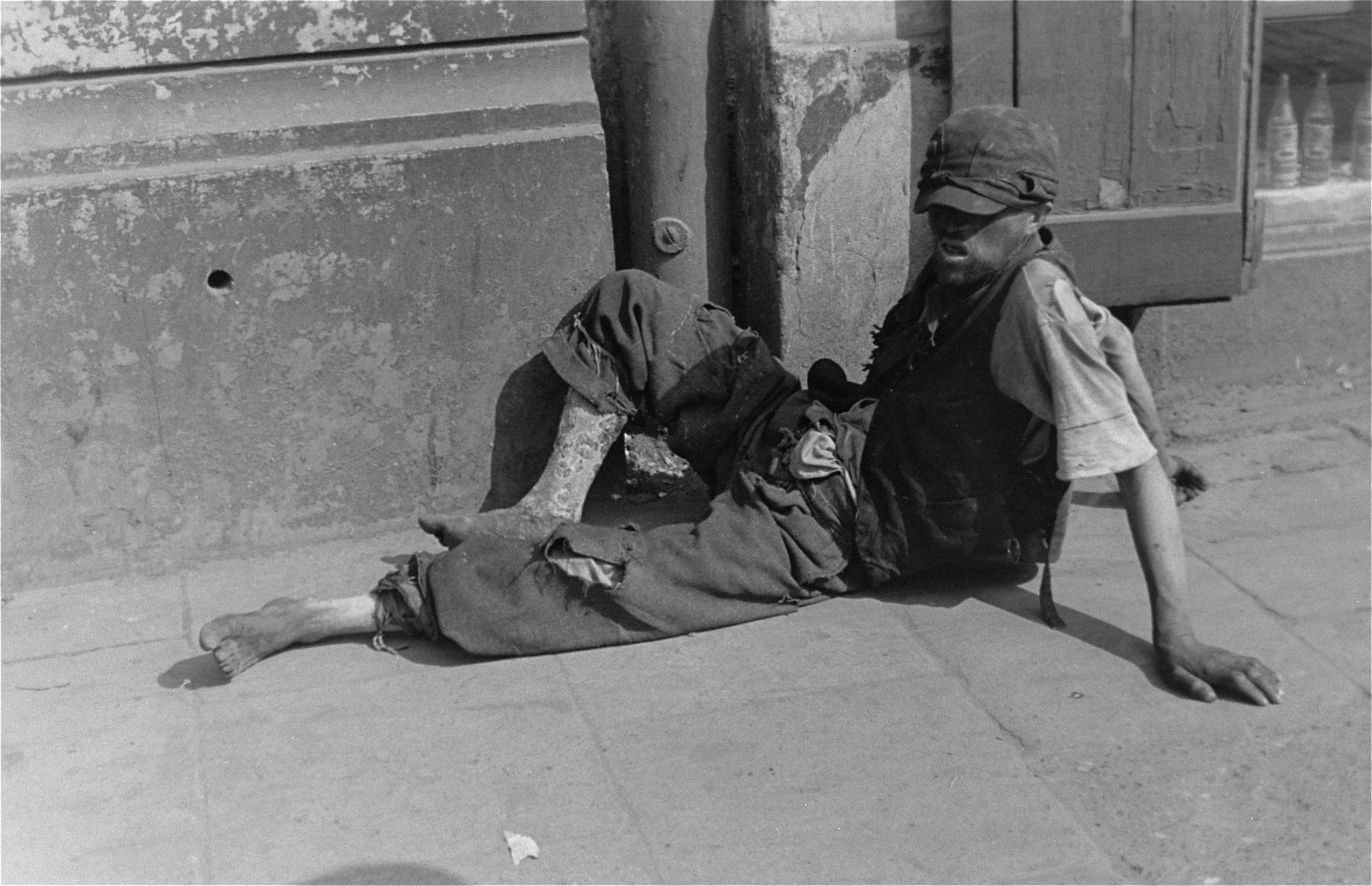 A destitute youth sits on the pavement in the Warsaw ghetto.