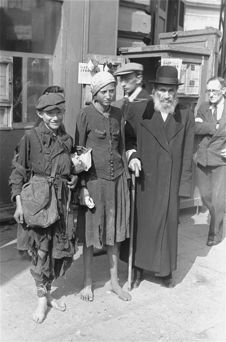 A religious Jew stands with two destitute youth on a street in the Warsaw ghetto.