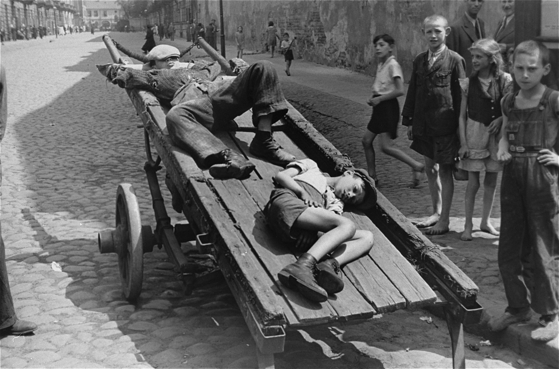 Two destitute boys sleep on a cart parked on a street in the Warsaw ghetto.