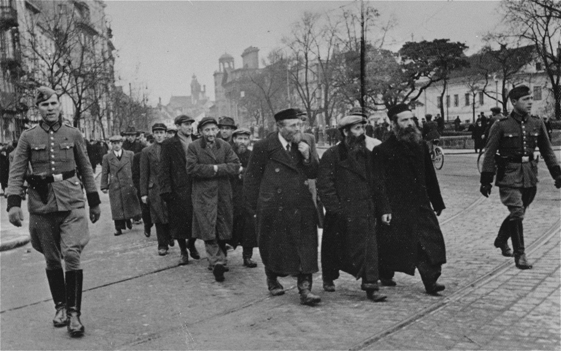 Jewish men who have been rounded-up by German police for forced labor are escorted along Krakowskie Przedmiescie Street to a worksite.