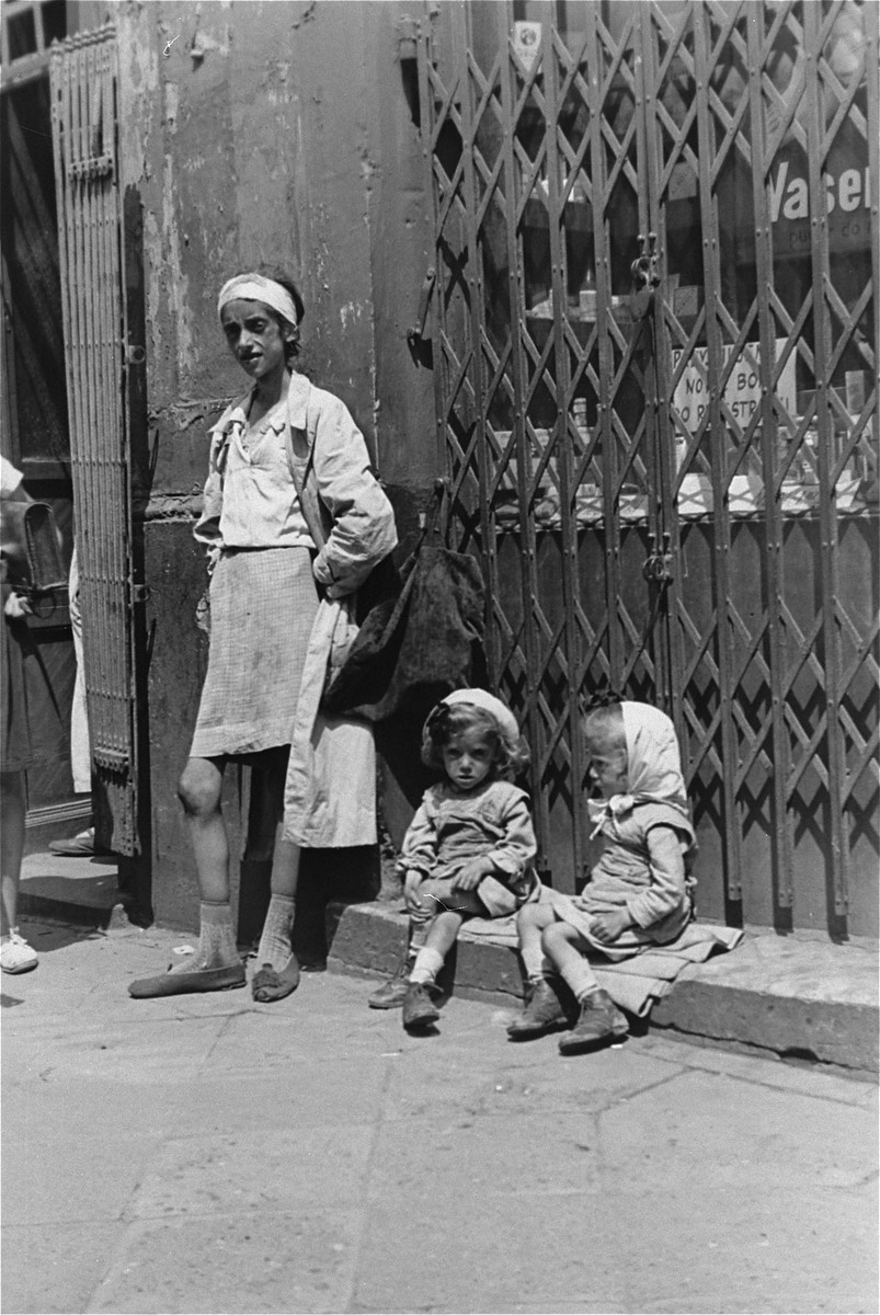 An emaciated woman stands in front of a closed shop in the Warsaw ghetto with two little girls.