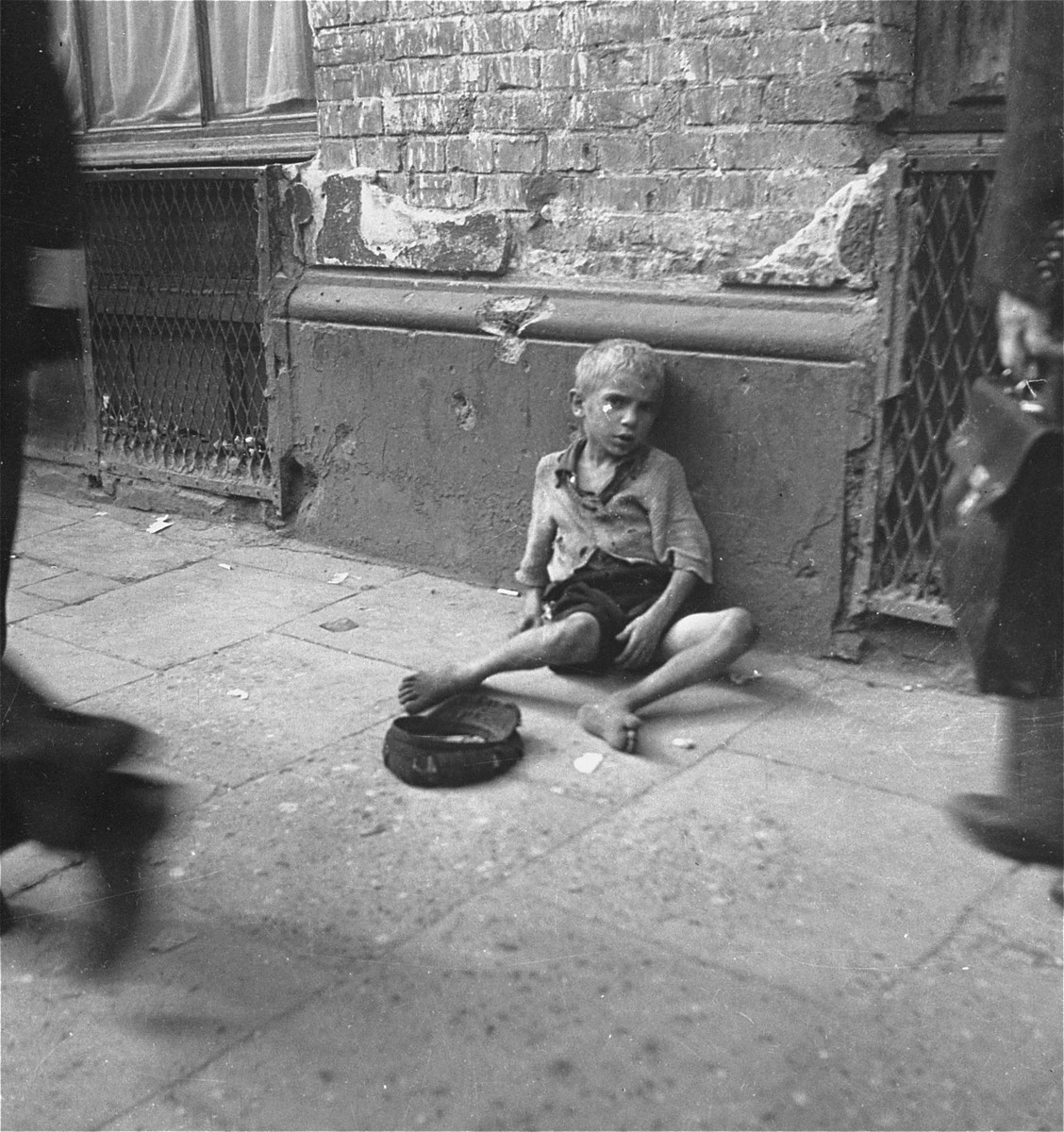 "A small boy begs on the sidewalk in the Warsaw ghetto.    Joest's original caption reads: ""They all expected nothing from me, the small beggars like this barefoot youngster with his hat on the street."""
