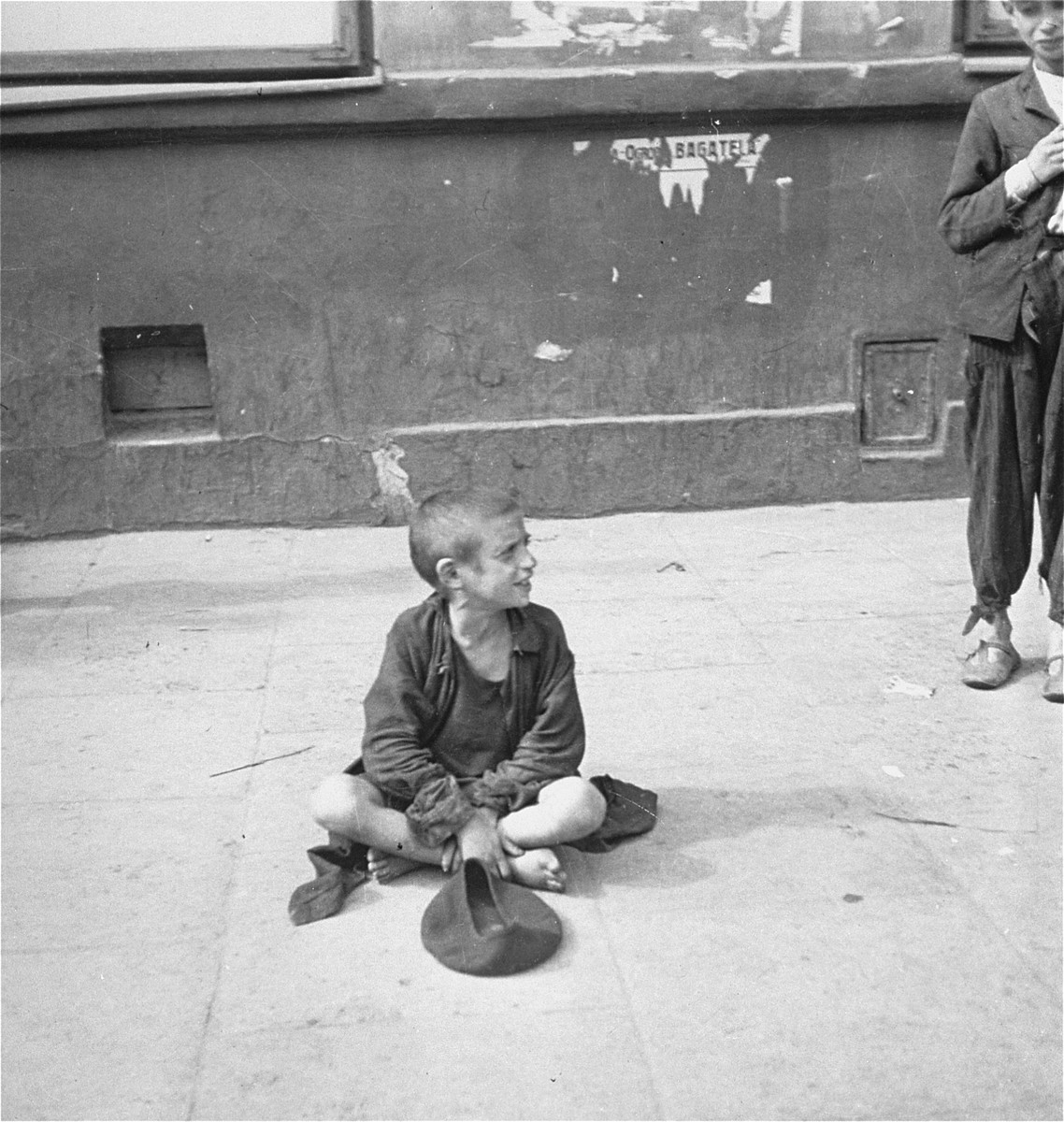 "A destitute child begs on a street in the Warsaw ghetto.  Joest's original caption reads:  ""I know this was on a 'good street,' meaning a central street with many pedestrians.  The child had a wound on his nose, but otherwise looked in good health.  However, he was barefoot, as were almost all [of the children], except for the boy next to him with his thin sandals who did not beg."""