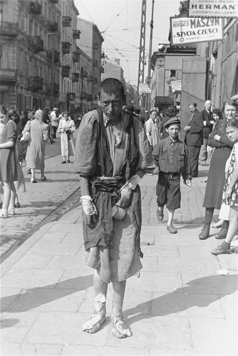 A bandaged, destitute Jewish youth walks along a street in the Warsaw ghetto.