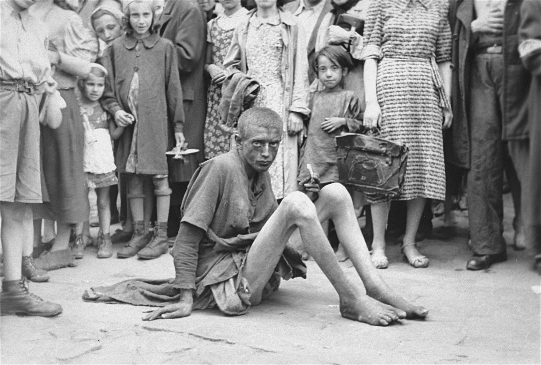 A destitute youth sits on the pavement in the Warsaw ghetto surrounded by other Jews.