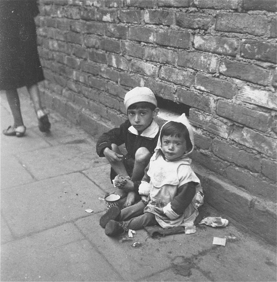 "Two children beg for food on the streets of the Warsaw ghetto.    Joest's original caption reads: ""I cannot say on which street this was.  They sat everywhere, these hungry children, and begged for a little money."""