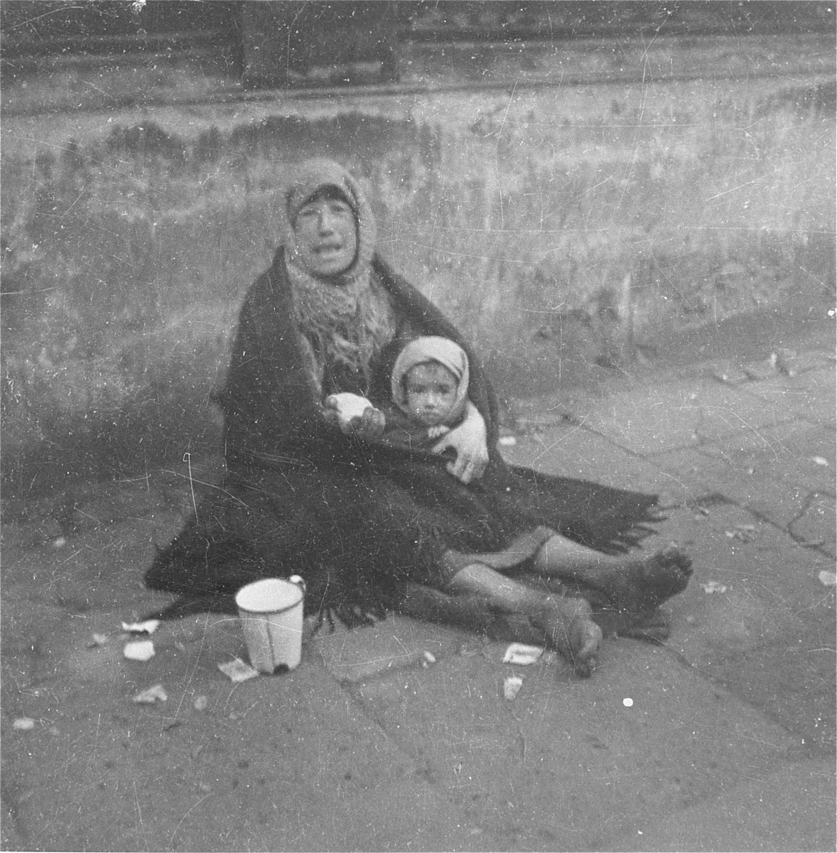 "A destitute mother holding her child begs on a street in the Warsaw ghetto.    Joest's original caption reads: ""With a gesture of her bandaged hand this woman wanted to show me that her child had nothing to eat.  She wore a headscarf wrapped in a blanket but had no shoes."""
