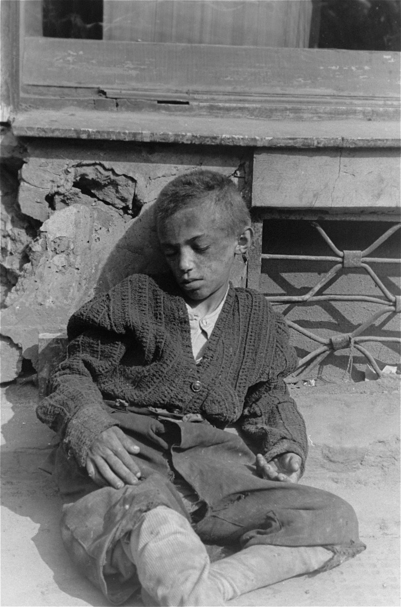 A destitute child sleeps on the pavement in the Warsaw ghetto.