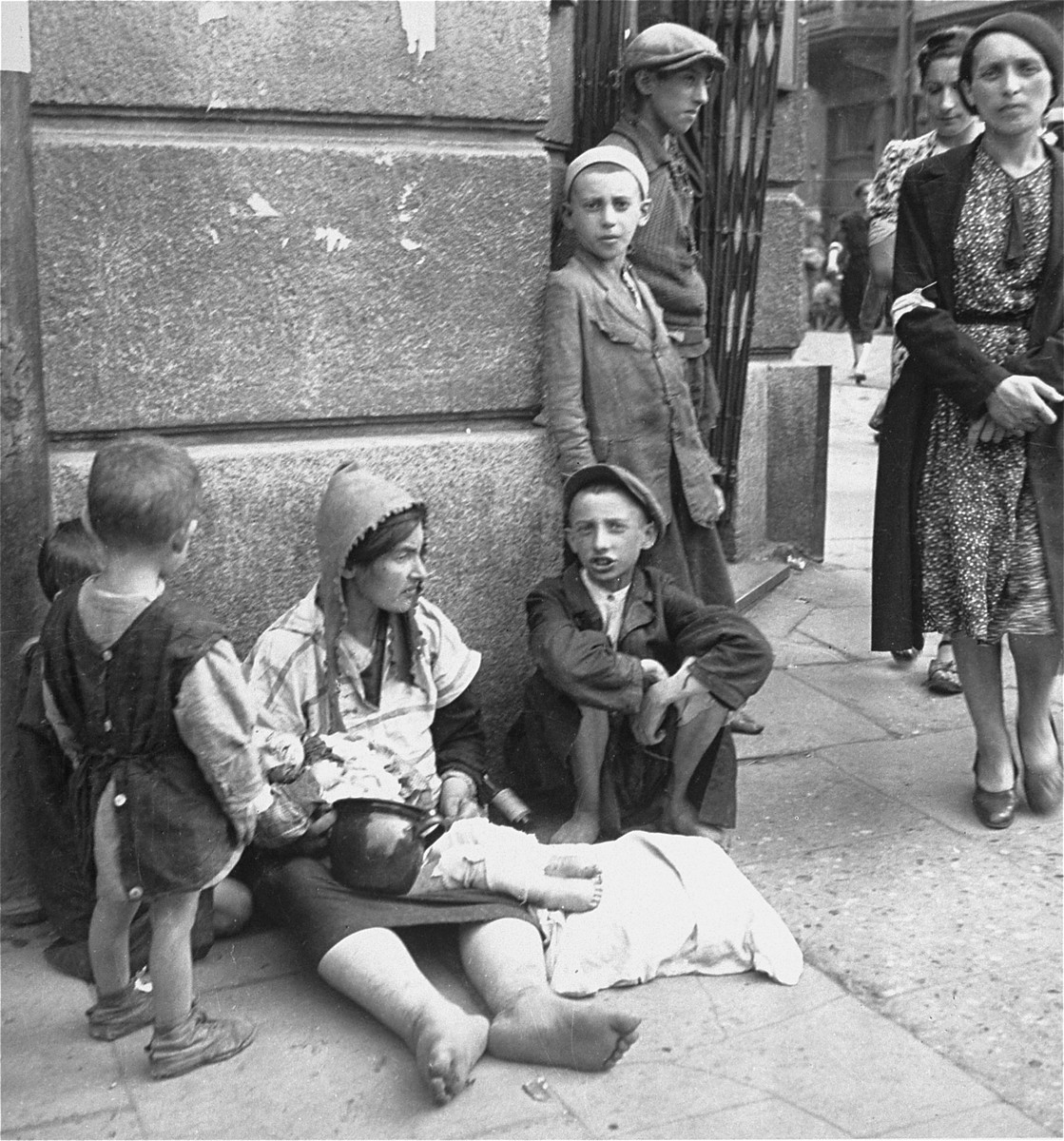 "A destitute woman and her children on a street in the Warsaw ghetto.    Joest's original caption reads: ""This was a common sight and I had reservations about photographing it: a woman with child that was deathly ill, [who] sat barefoot and begging on the street.  She did not notice me."""