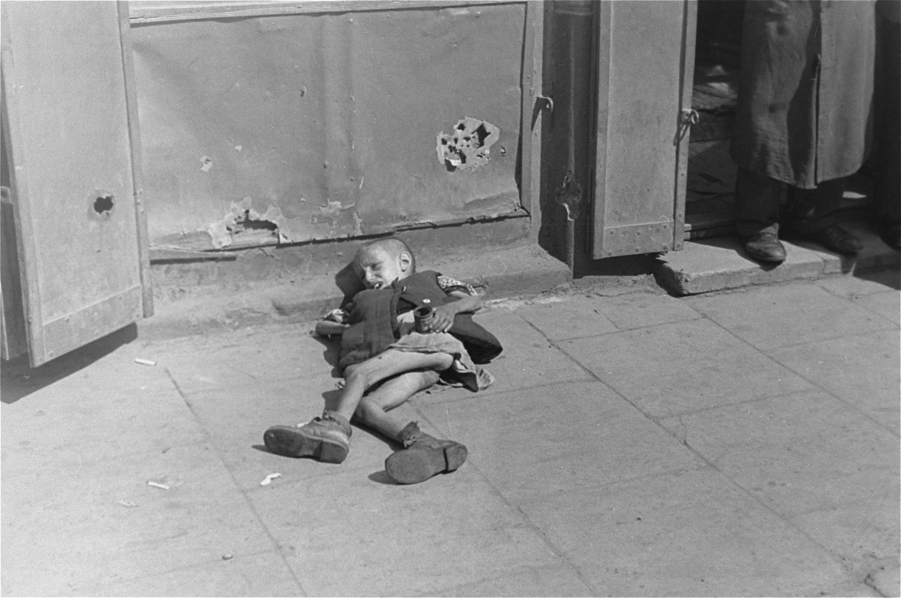 A destitute young boy lies on the pavement in the Warsaw ghetto holding a cup in his hand.