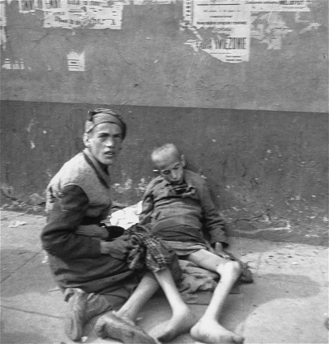 "Two young women, one of whom is unconscious, on the street in the Warsaw ghetto.    Joest's caption reads: ""Under ripped advertisements an unconscious woman lay against the wall.  Another person attempted to care for her.  She looked at me as if she expected me to help."""