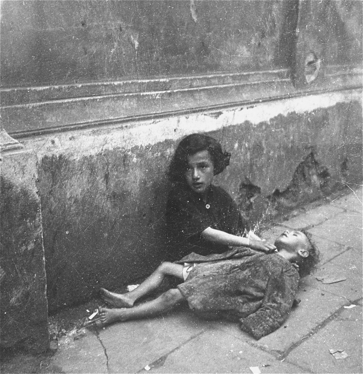 "A destitute little girl comforts her little sister, who lies unconscious in her lap.    Joest's original caption reads: ""These were clearly sisters.  If the younger one was dead, I could not say.  She did not move."""