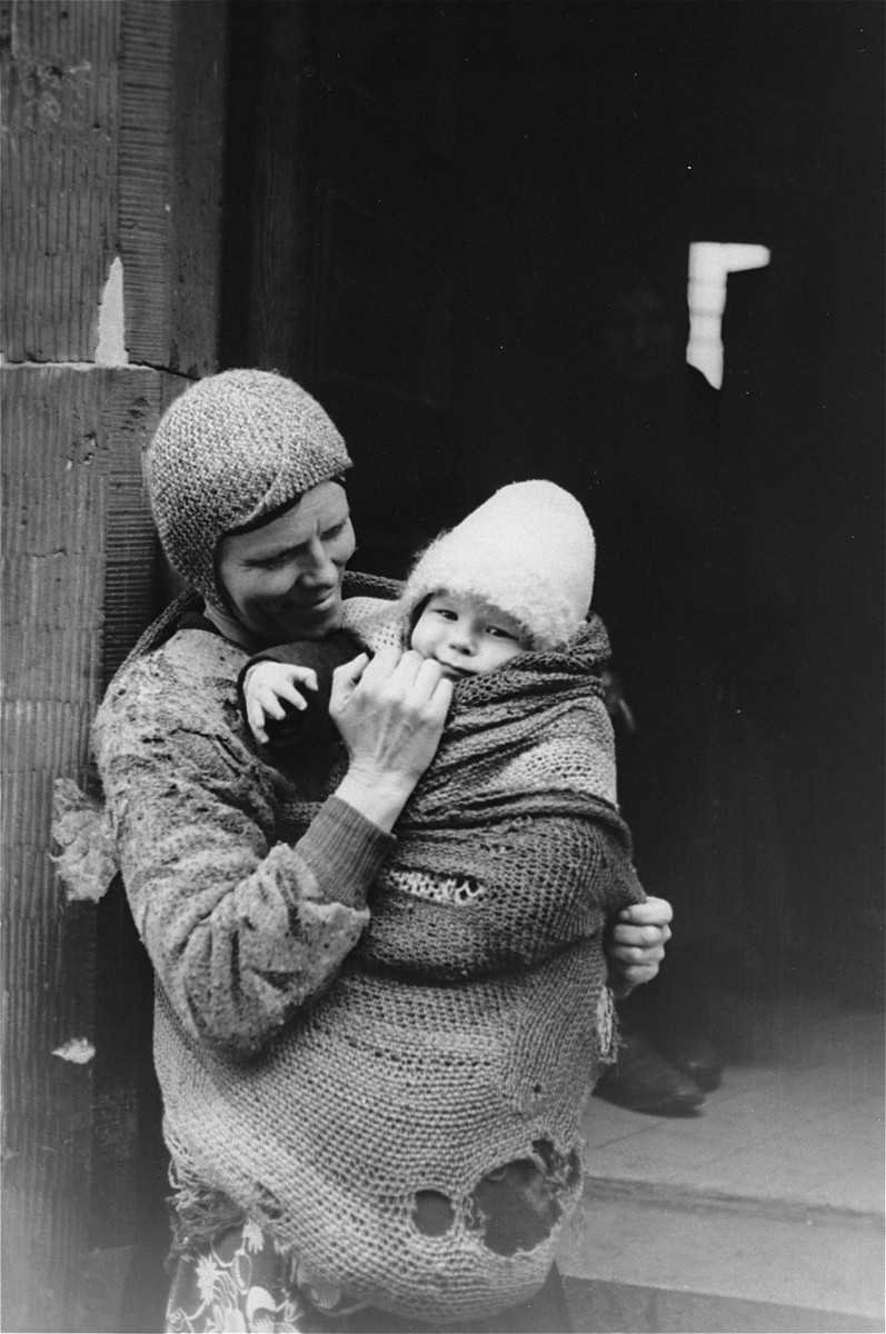 A destitute mother holds a child swaddled in a ragged blanket on a street in the Warsaw ghetto.