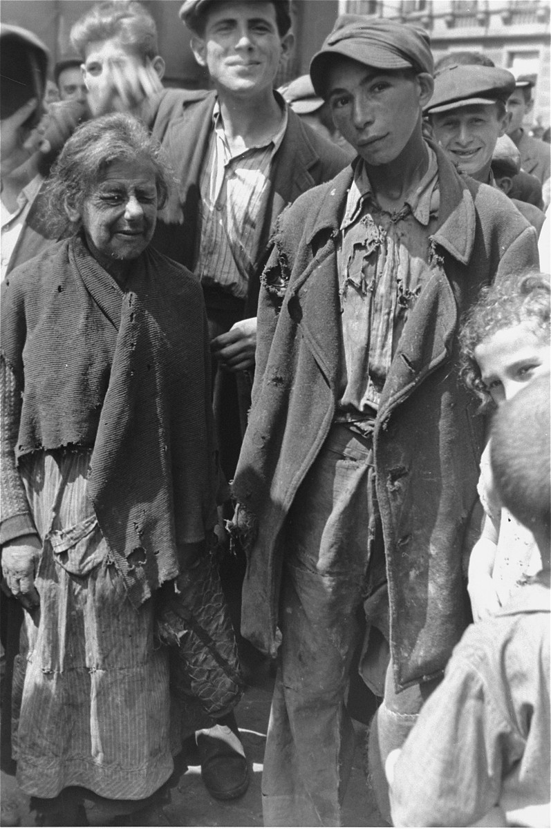 Two destitute Jews stand among a crowd of people on a street in the Warsaw ghetto.