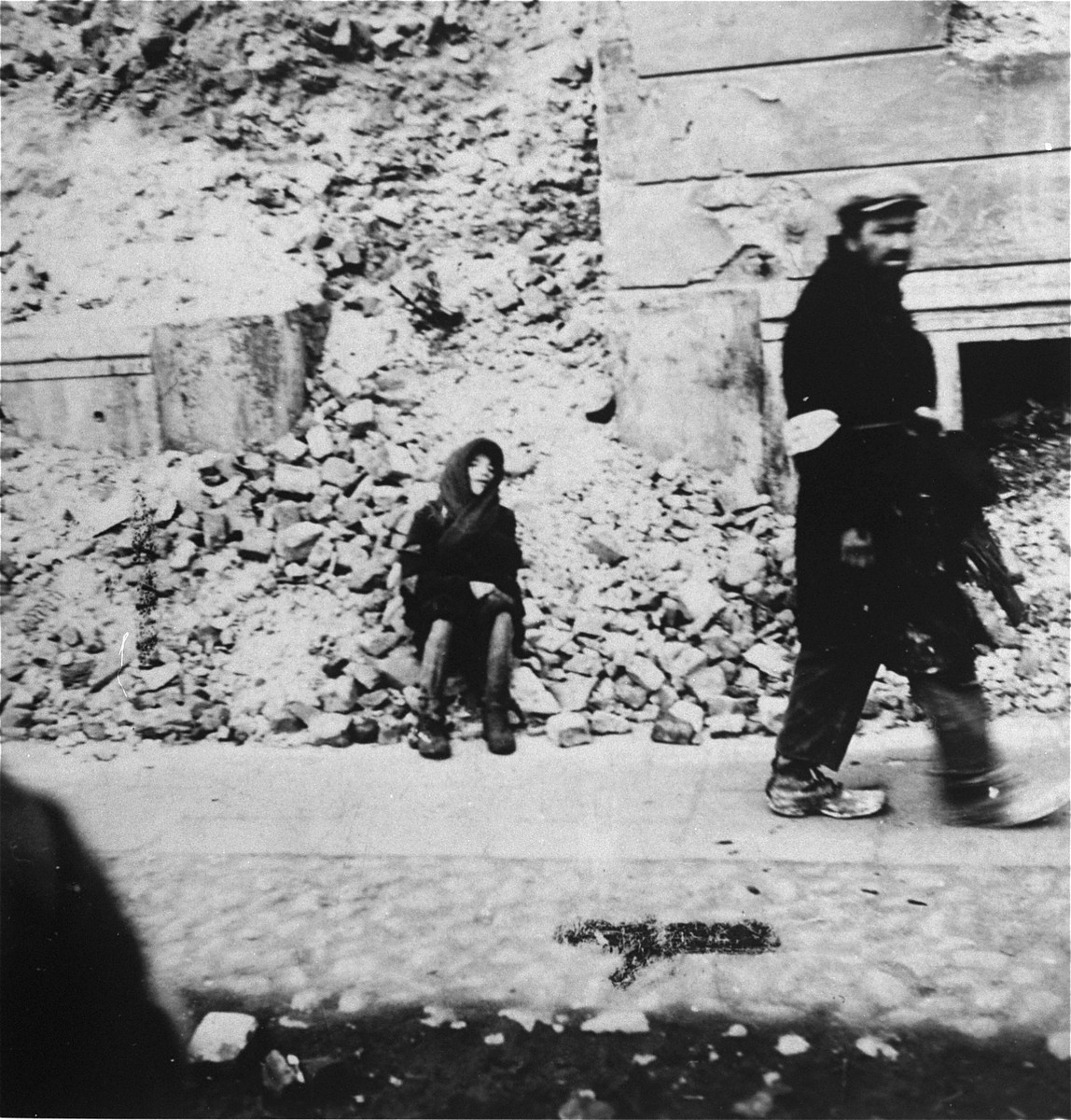 A destitute child sits on the ruins of a building in the Warsaw ghetto while another man walks by.