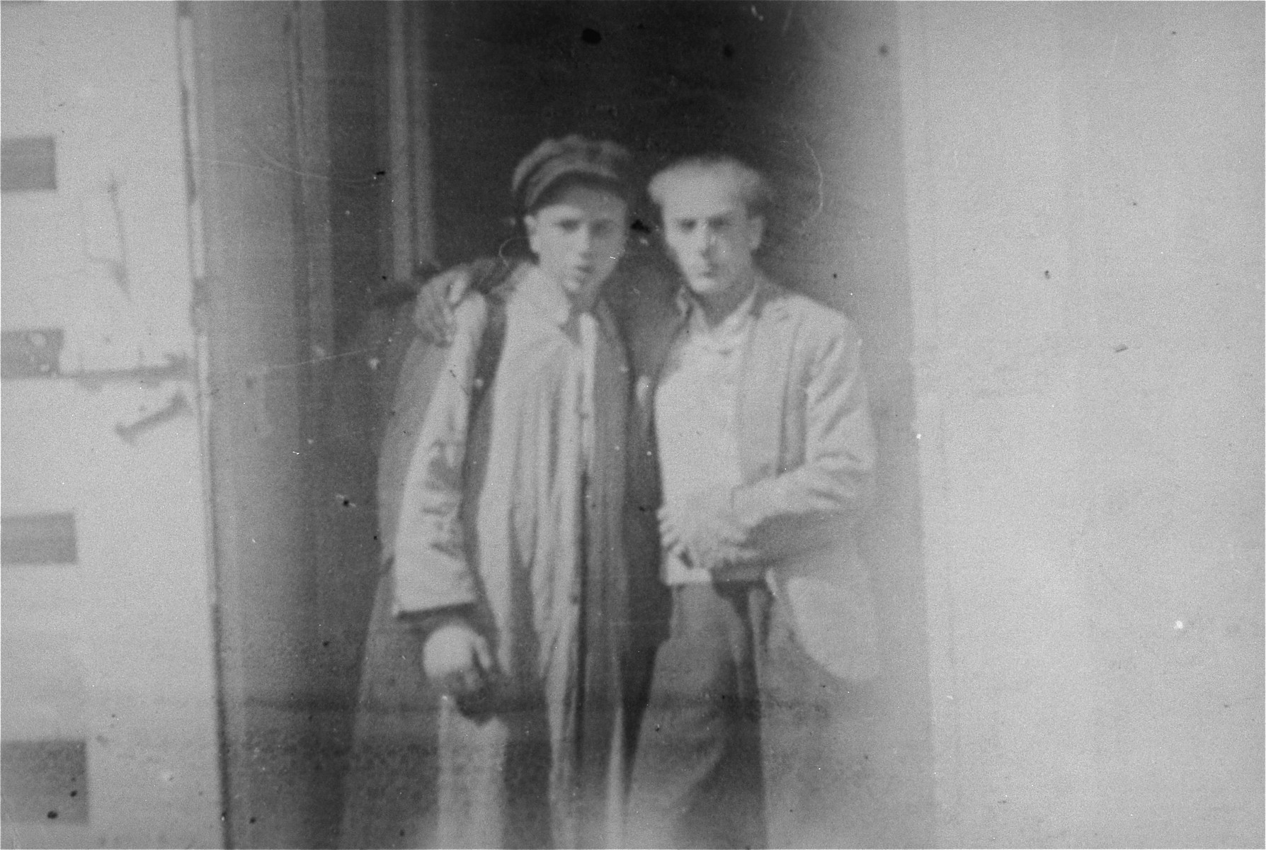 Two Jewish youth who are posing as Poles stand outside in a doorway on the Aryan side of Warsaw.  Pictured are Ignacy (Byczek) Milchberg (left) and Izaak (Zbyszek) Grynberg (right), two of a group of 20 Jewish children who were living in hiding on the Aryan side of Warsaw and supporting themselves by selling cigarettes in Three Crosses Square.