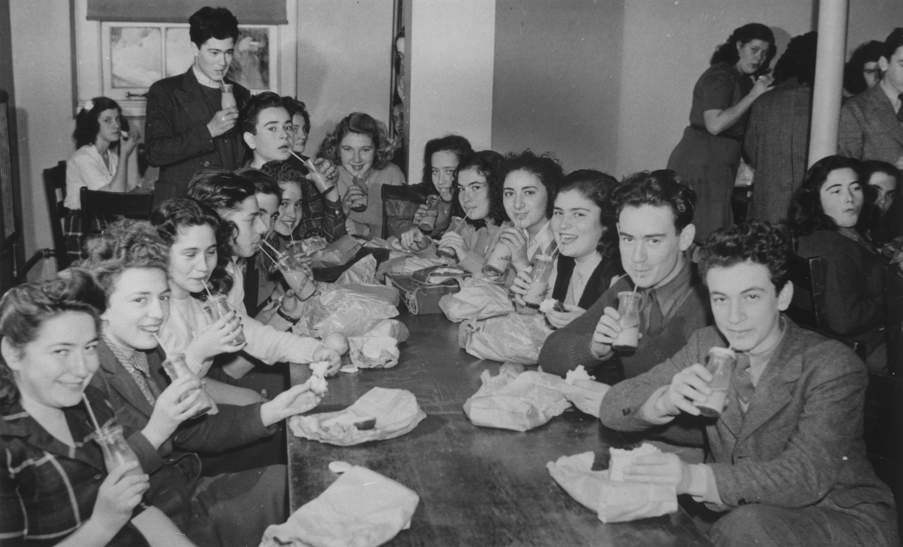 Refugee youth pose with milk bottles and bag lunches in a dining room at the Fort Ontario refugee shelter.   Among those pictured are left side: Edith Broner, Silvio Levy, Ernest Spitzer, Lili Broner, Bruno Kaiser and Ivo Svecenski.  Right side: Herman Kremer, David Hendel, Thea Weiss and Neli Bokros.  Table on right: Lea Hanf.