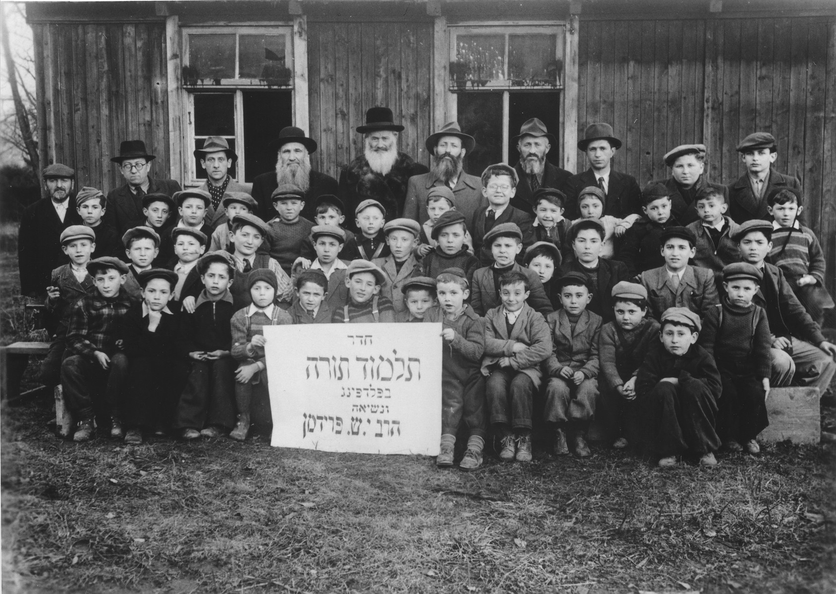 Group portrait of students and teachers of the Talmud Torah (religious primary school) in the Feldafing displaced persons camp.  Among those pictured is Srulek Rajs.