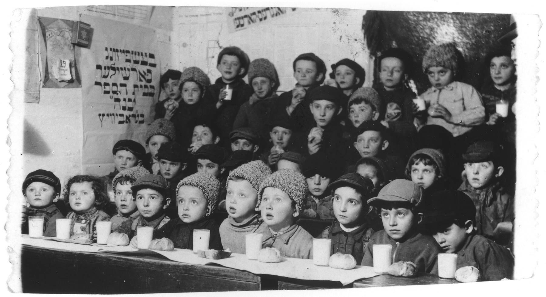 Group portrait of young Jewish children having a snack at the Yavneh Hebrew school in Grabowiec.  Lila Rajs, the only girl in the class, is seated second from the left.