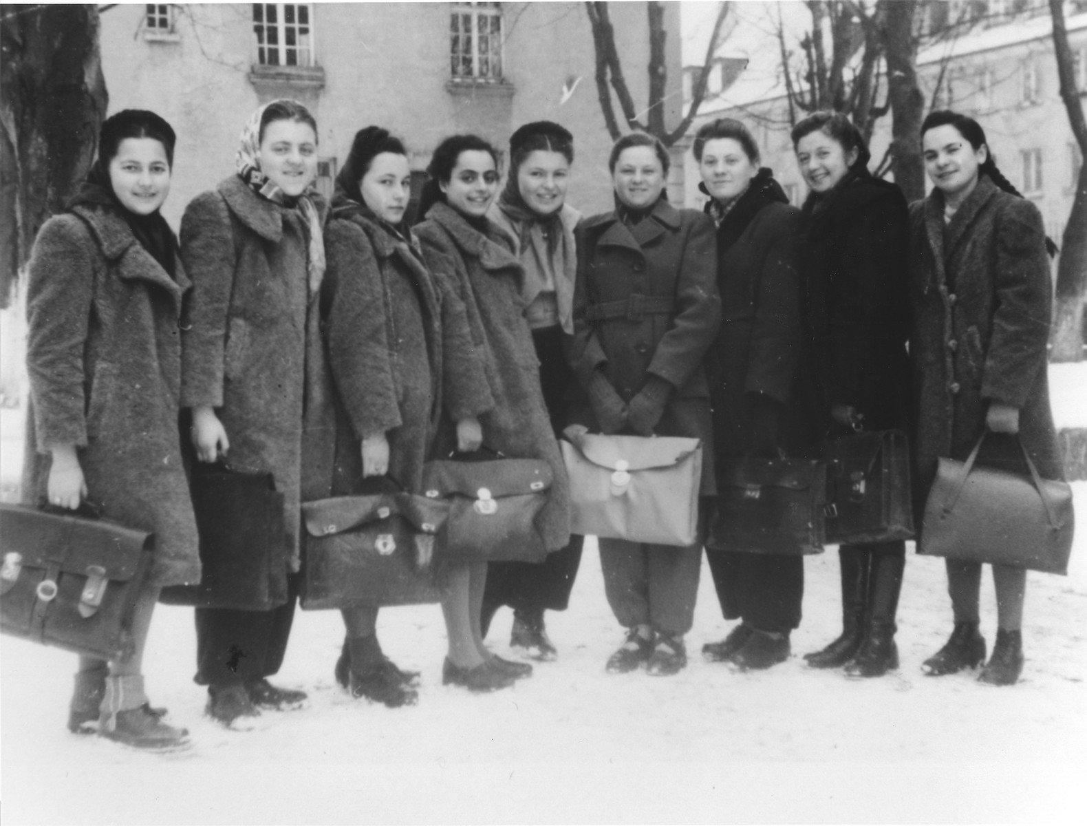 A group of teenage girls carrying briefcases pose on a snowy street on their way to their high school.  Among those pictured are Ruzia Rozen (left), Lila Rozen (third from the left) and Lila Rajs (center).