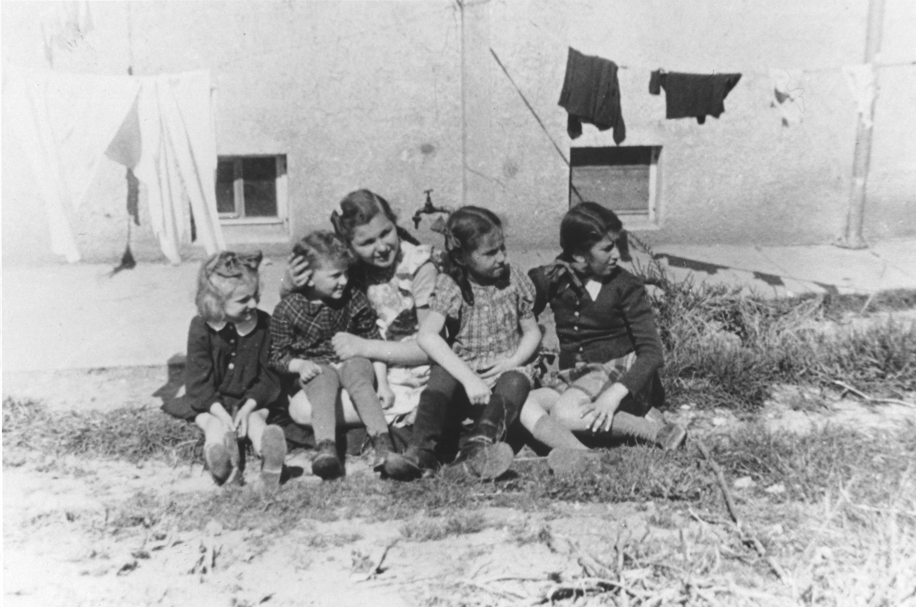 A group of children sit behind a barracks in the Ulm displaced persons camp.  Among those pictured is Lila Rajs (center) and Yanka Galler (far right).