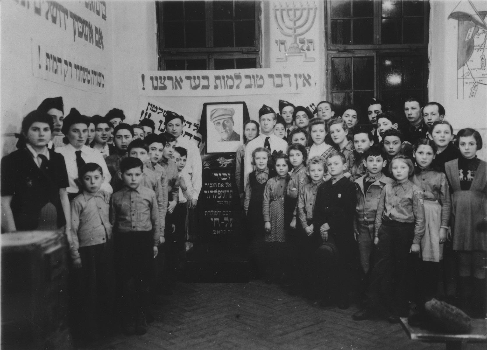 """Members of the Betar revisionist Zionist youth movement pose alongside a memorial display featuring a portrait of Joseph Trumpeldor and a Hebrew plaque that reads, """"There is nothing better than to die for our land"""".  Among those pictured are Ida Wulach, Surele Greenblat and Lila Rajs."""
