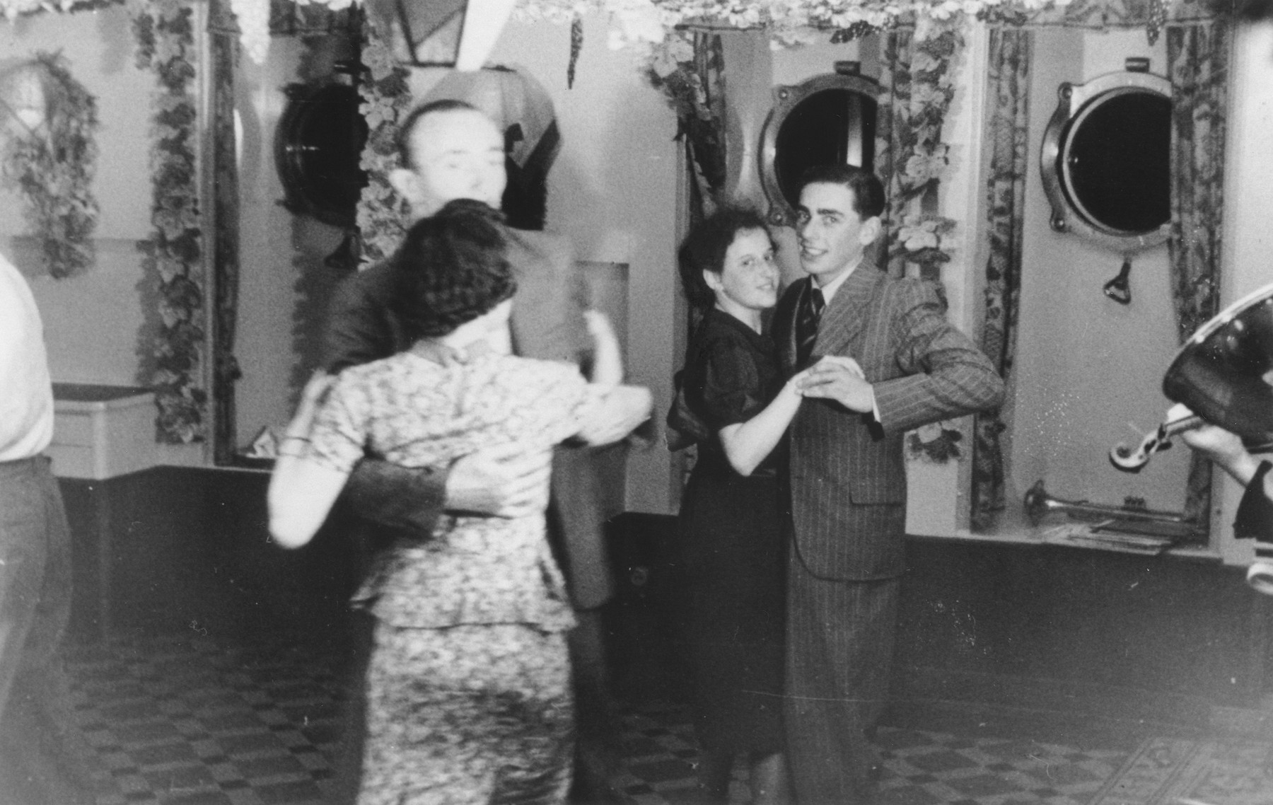 Jewish refugees on board the MS St. Louis dance in the ballroom.  Pictured on the right are Fritz Buff and Vera Hess.