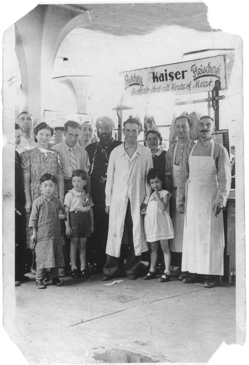 German Jewish refugees pose with local residents in Siegfried Kaiser's butcher shop in Shanghai.  Among those pictured are Siegfried Kaiser (second from the right); his brother-in-law, Alfred Eisen (center); Ruth and Sonja Kaiser (between Siegfried and Alfred).