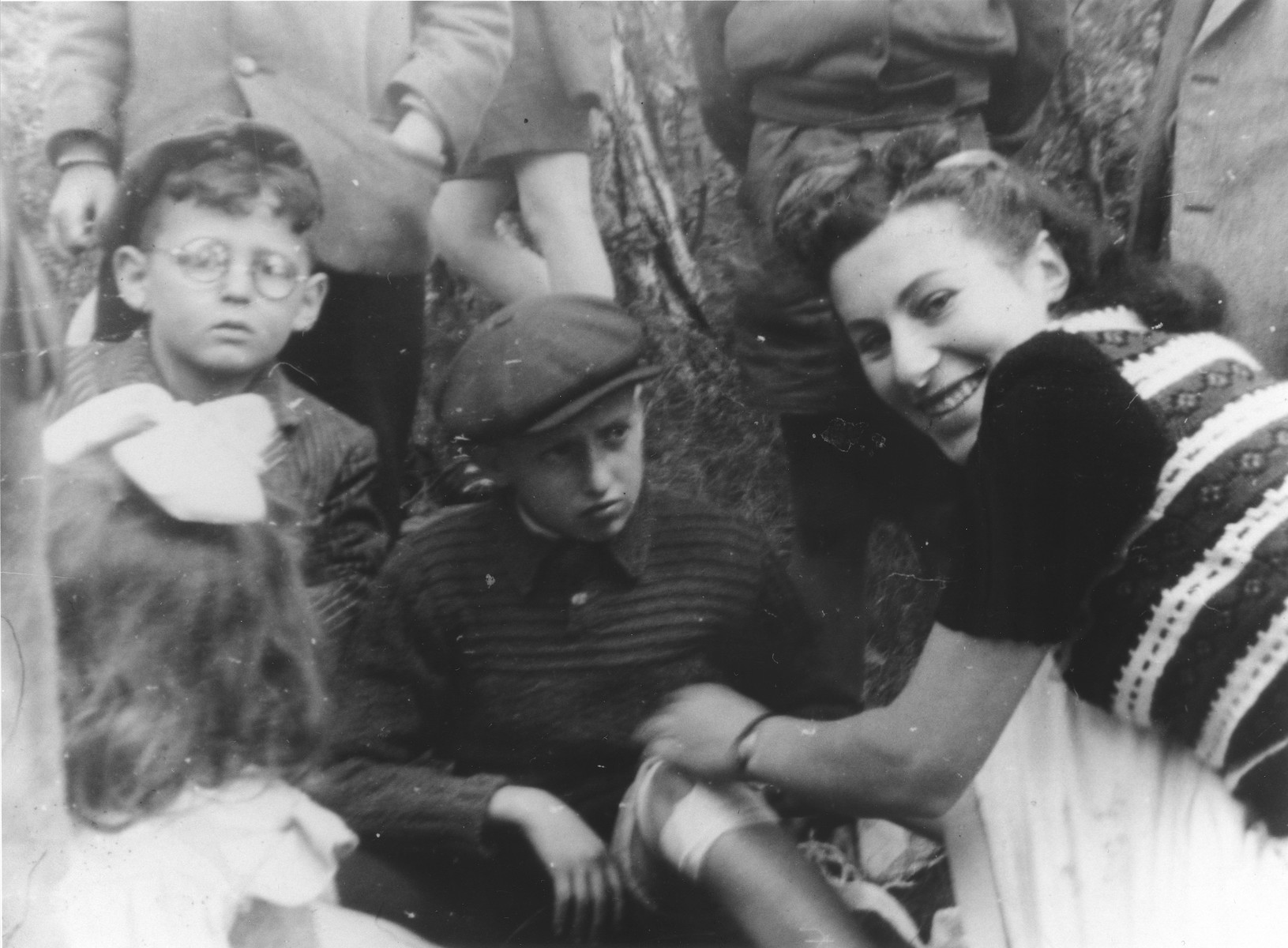 A Red Cross worker bandages a child's leg in the Ulm displaced persons camp.  Srulek Rajs is pictured on the far left.