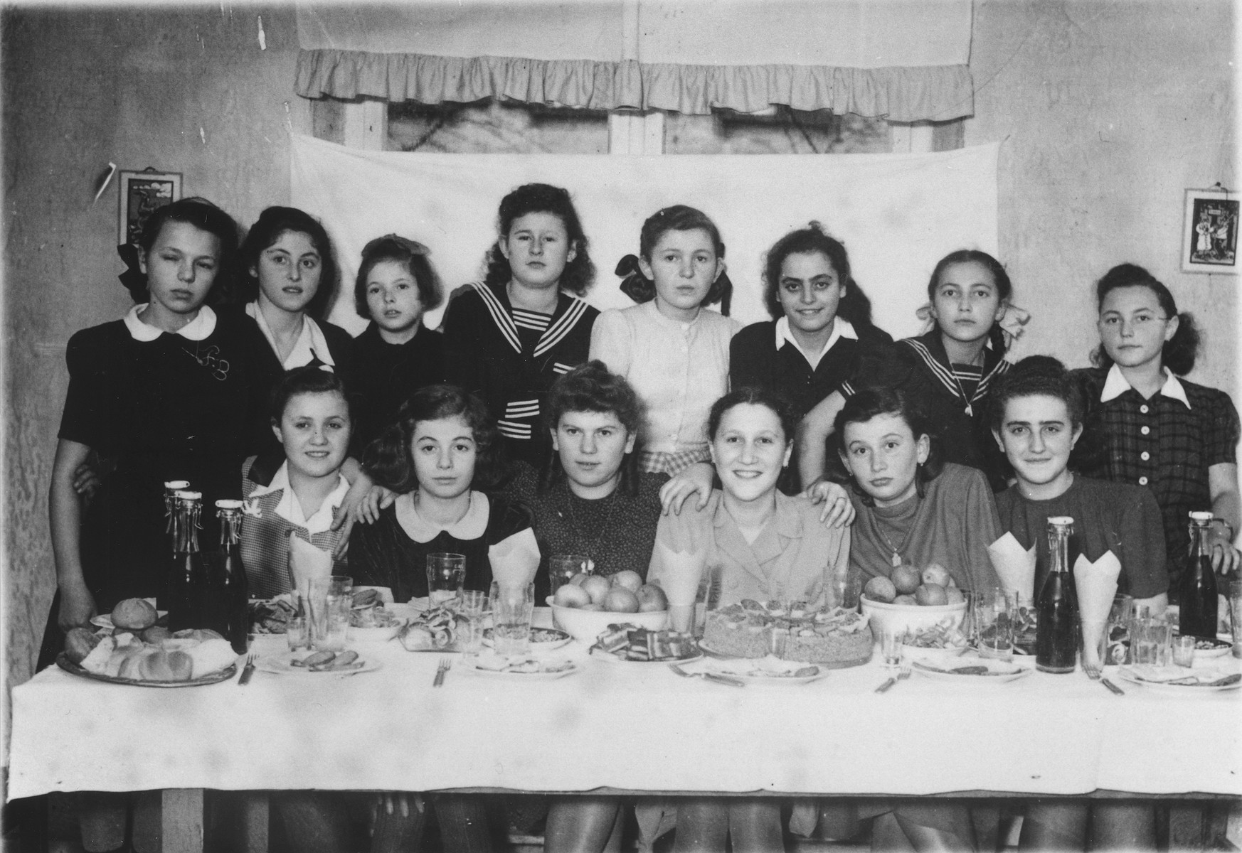 Group portrait of Jewish girls at Ida Wallach's birthday party in the Ulm displaced persons camp.  Among those pictured are Rochela Gellman, Surele Greenblat, Ida Wullach, Regina Yablonska, Lila Rajs, and Ruzia and Lila Rozen.