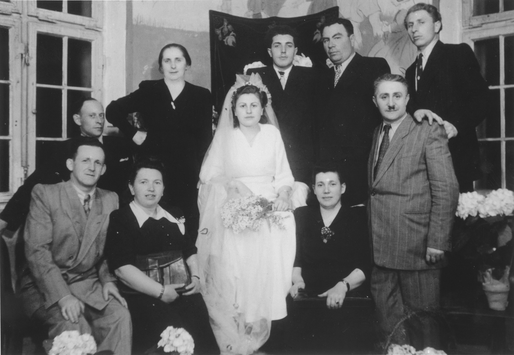 Group portrait of members of a wedding party in the Ulm displaced persons camp.  Among those pictured are Hershel and Chaja Rajs (bottom left).