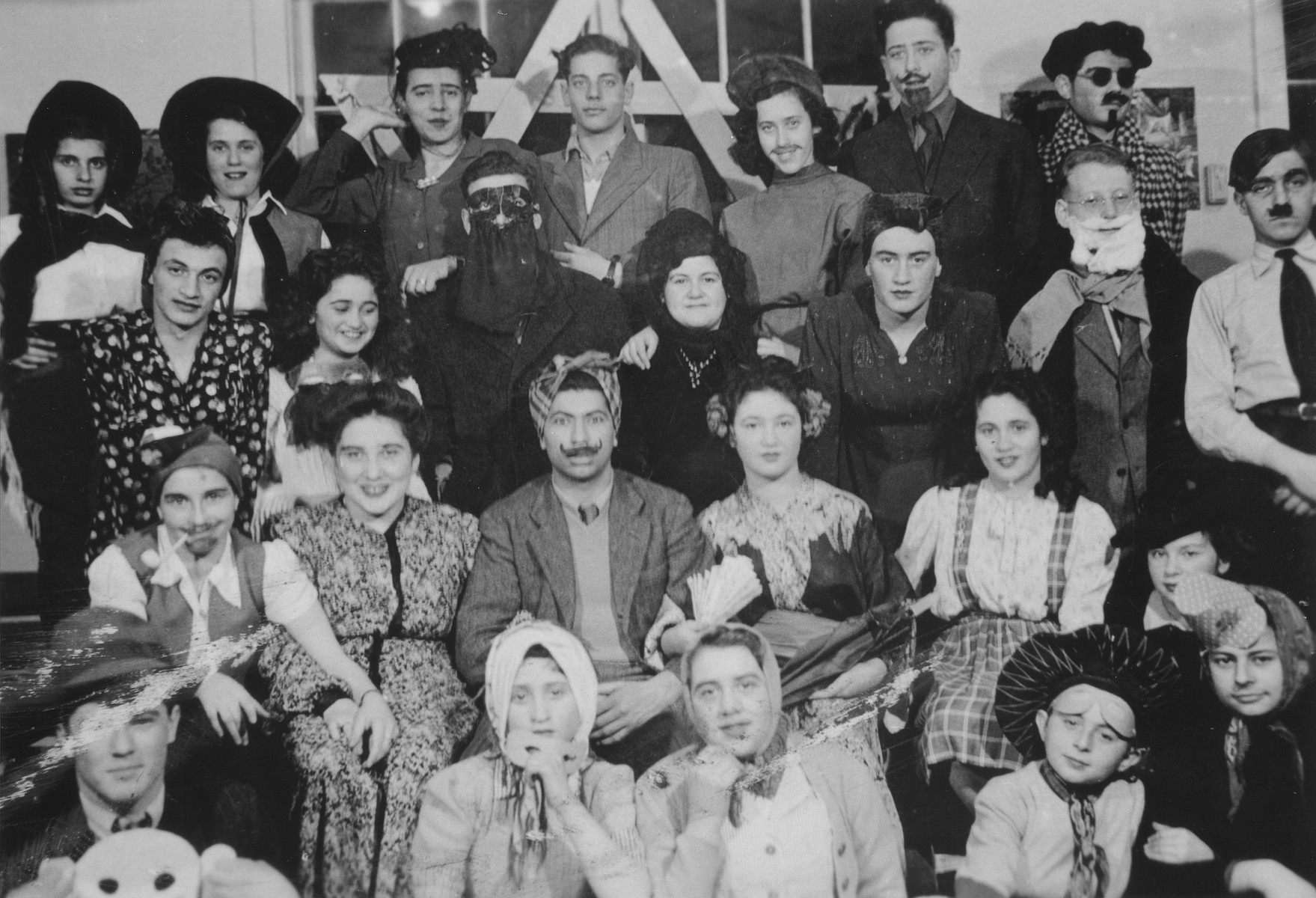 Group portrait of Jewish youth dressed in Purim costumes at the Fort Ontario refugee shelter.  One of them is dressed as Adolf Hitler.   Left to right (front row) Ivo Svencenski, Jacob Broner, unknown, unknown and Leo Levic.  Second row: Liesel Bader, Henny Notovitz, Edward Levic, Neva Svecenski, Edith Broner and Elfi Strauber.  Third row: Herman Kremer, Manci Broner, unknown, Lillian Danon, Ralf Kuznitzki, and Ivo Lederer in the Hitler costume.  Back row: Dorit Reisner, Ginette Cygelman, Adam munz, Silvio Levy, Neli Bokros, Paul Bokros, and Paul Arnstein.