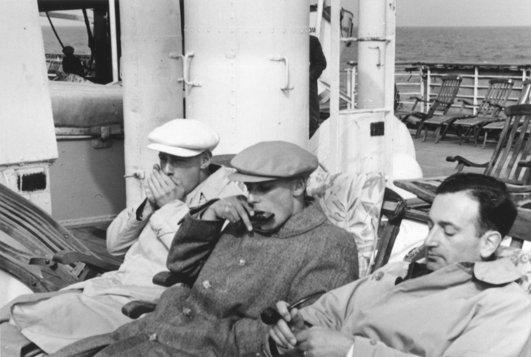 Three young Jewish refugees relax on the deck of the MS St. Louis.  Werner Lenneberg (right) naps while Fritz Buff (center) and another friend play harmonicas.