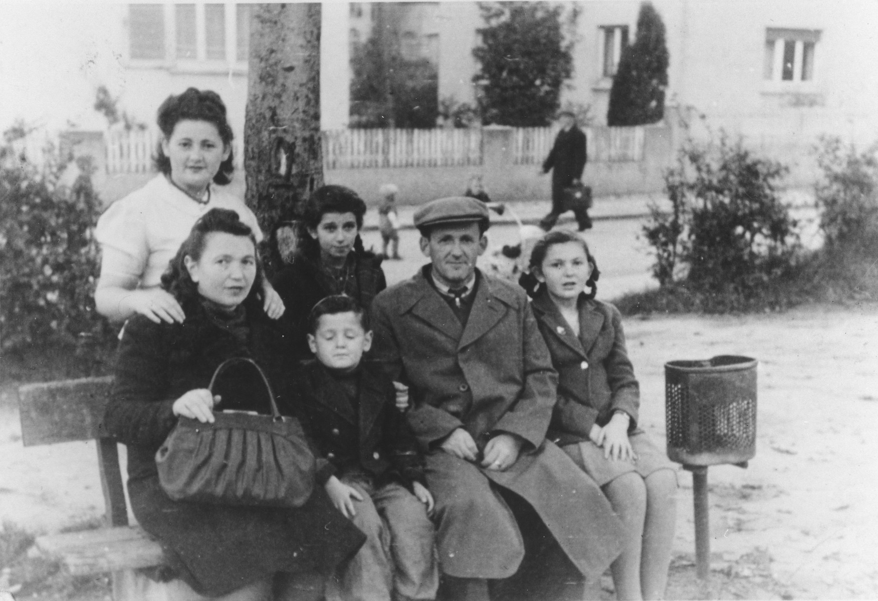 The Rajs family poses on an outdoor bench in the Ulm displaced persons camp.  Standing left to right are Chuma Rajs and Yanka Galler.  Seated left to right are Chaja, Srulek, Hershel and Lila Rajs.