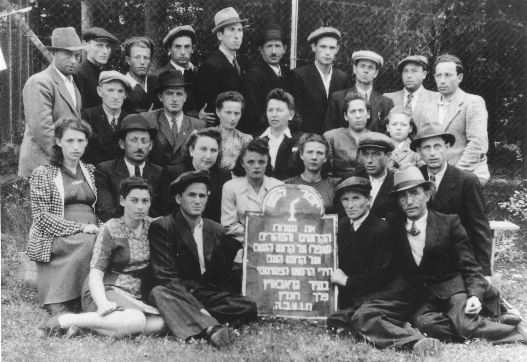Group portrait of Jewish survivors from Grabowiec with a plaque commemorating those who were killed by the Nazis.  Among those pictured is Chaja Rajs (seated in the center in a dark suit and white blouse).