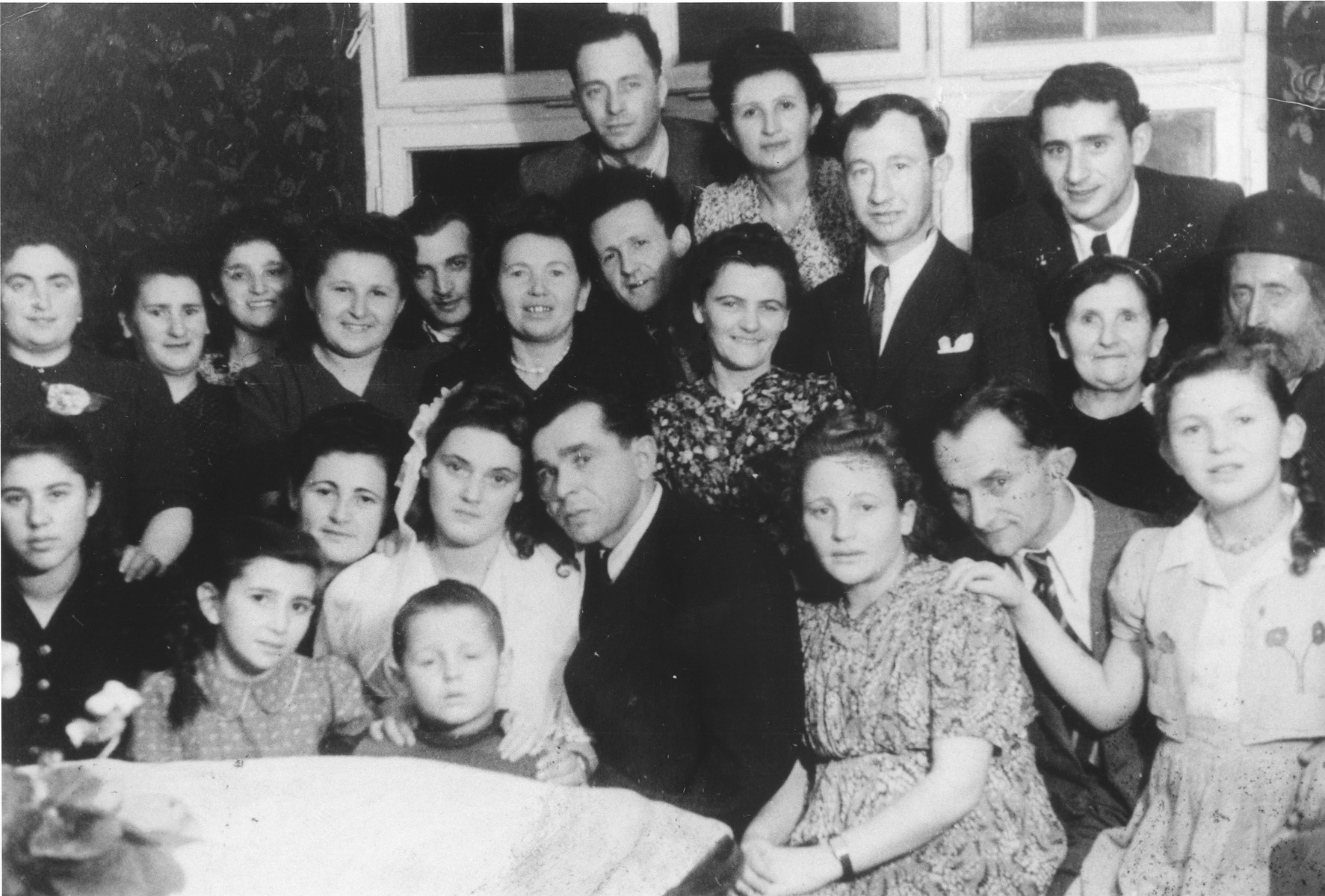 Group portrait of family and friends at the first wedding in the Ulm displaced persons camp. The bride and groom are Dzunia and Joe (Yitchak) (Itche) Storch.   Also pictured from right to left n the front row are: Lila Rajs, Meyer Fenig and Bina (Rajs) Fenig.  Chuma (Rajs) Fruchter is seated next to the bride on the left.  Directly behind the bride is Chaja Rajs.  To the right of Chaja are Hershel Rajs and Roshi (Rajs) Binder.  Behind them are Moishe Binder and Moishe Fruchter.