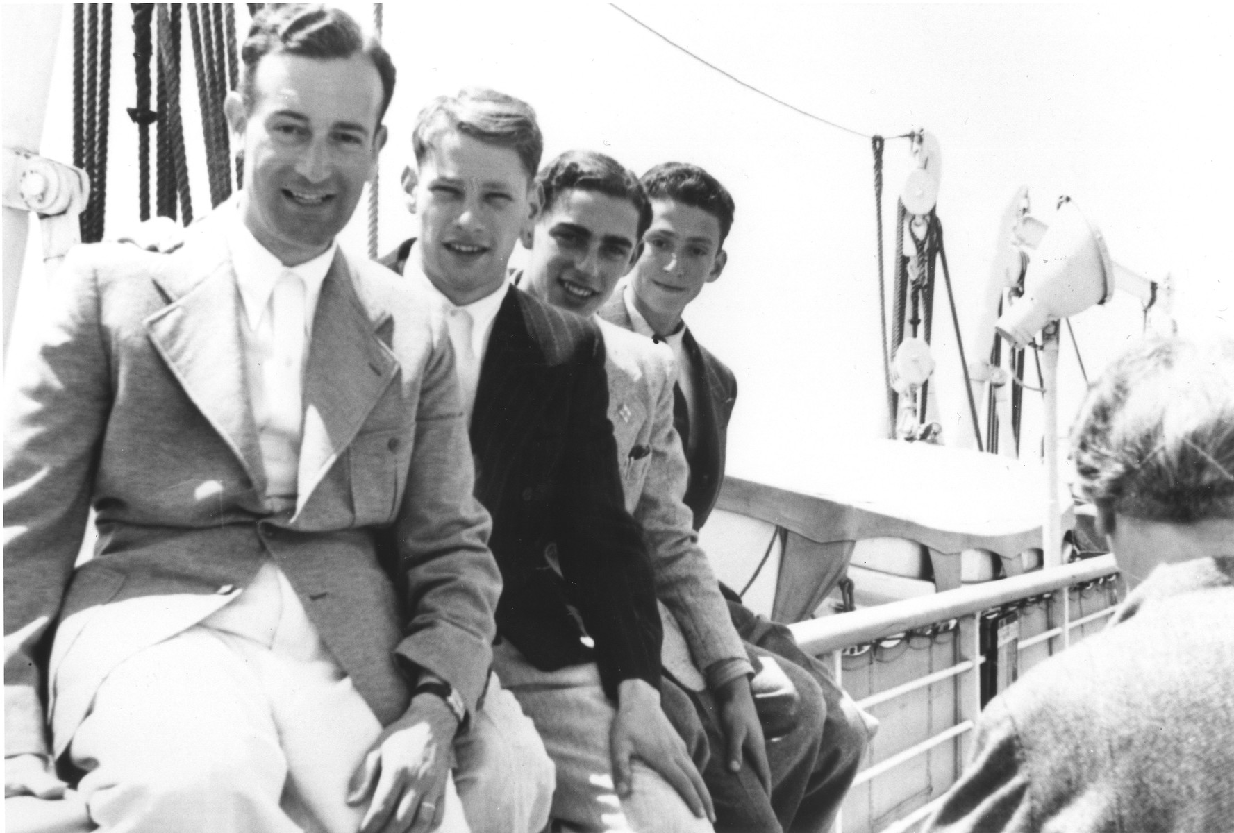 Four young Jewish refugees sit on the railing along the deck of the MS St. Louis.  Pictured from left to right are Werner Lenneberg, Fritz Hilb, Fritz Buff and unknown.