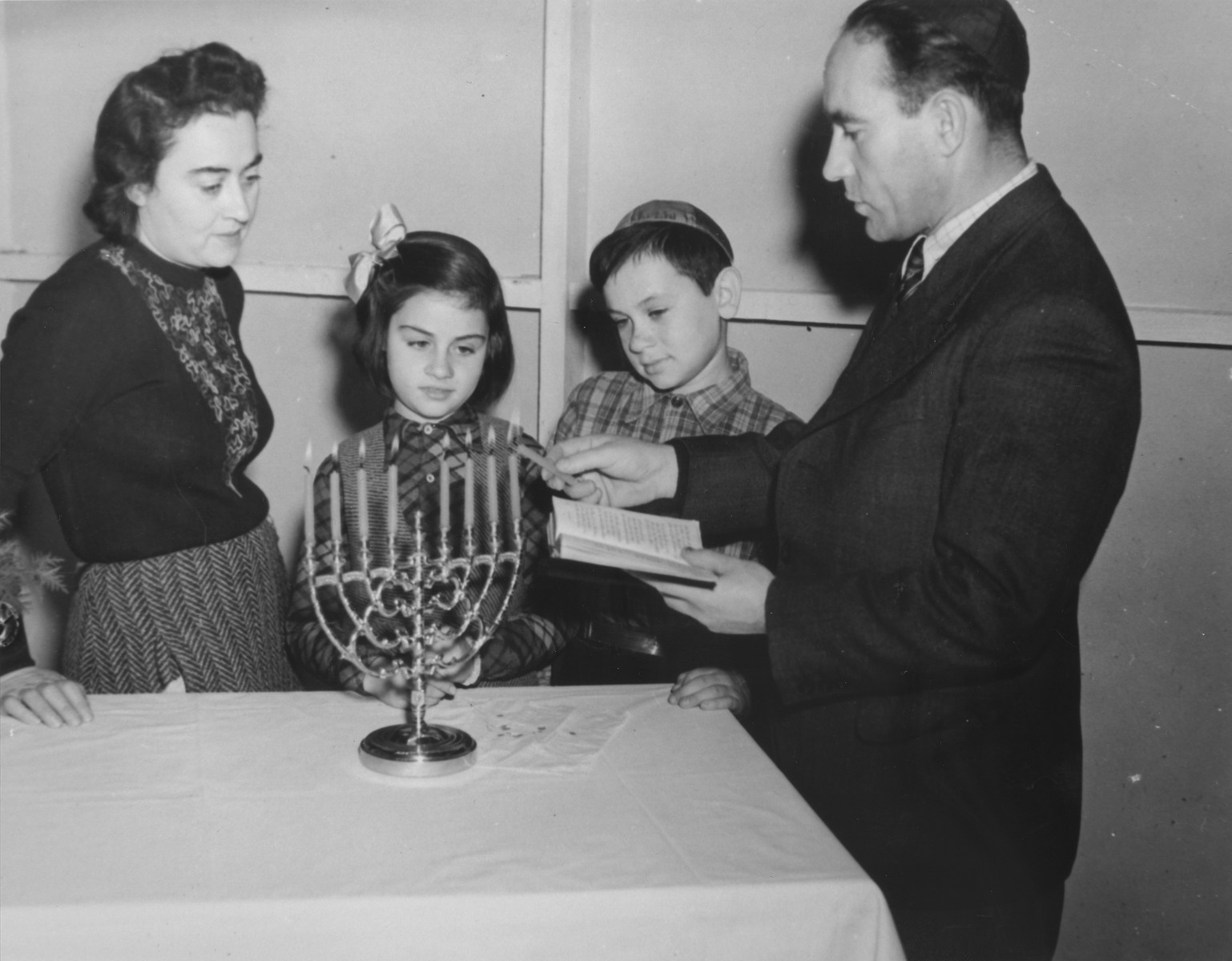 A Jewish refugee family lights a Hanukkah menorah in their room at the Fort Ontario refugee shelter.  Pictured are Eisig and Hana Hendel, their daughter Ruth, and nephew Vilko Kremer.