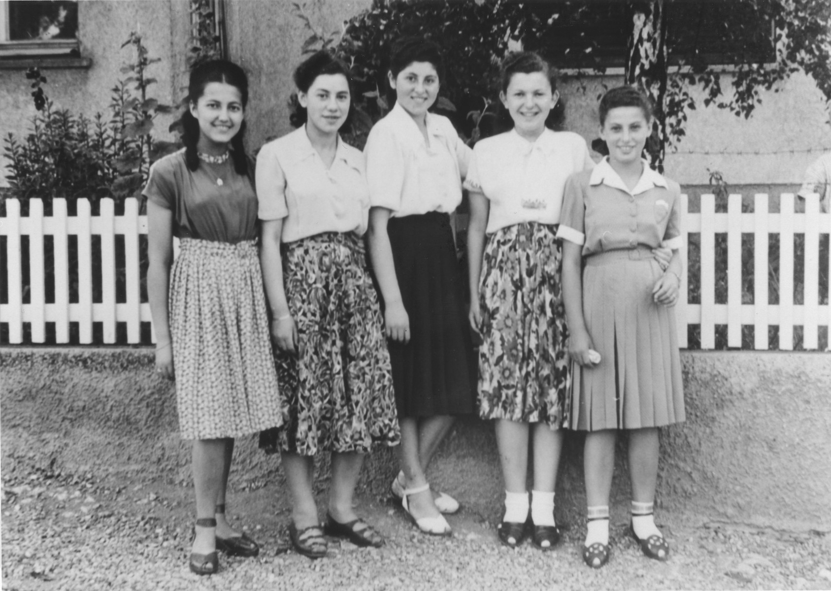 Five young Jewish women pose in front of a fence in the Ulm displaced persons camp.  Pictured from left to right are Lila Rozen, unknown, Regina Yablonska, unknown and Lila Rajs.