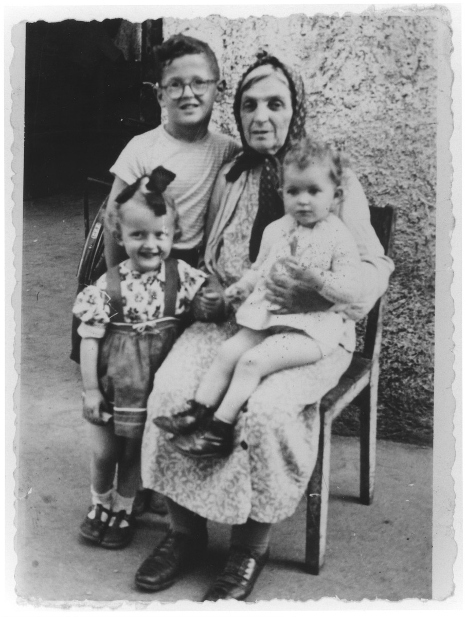 Portrait of Sheindl Rajs in the Ulm displaced persons camp surrounded by her grandchildren Srulek, Rivka and Gitele.