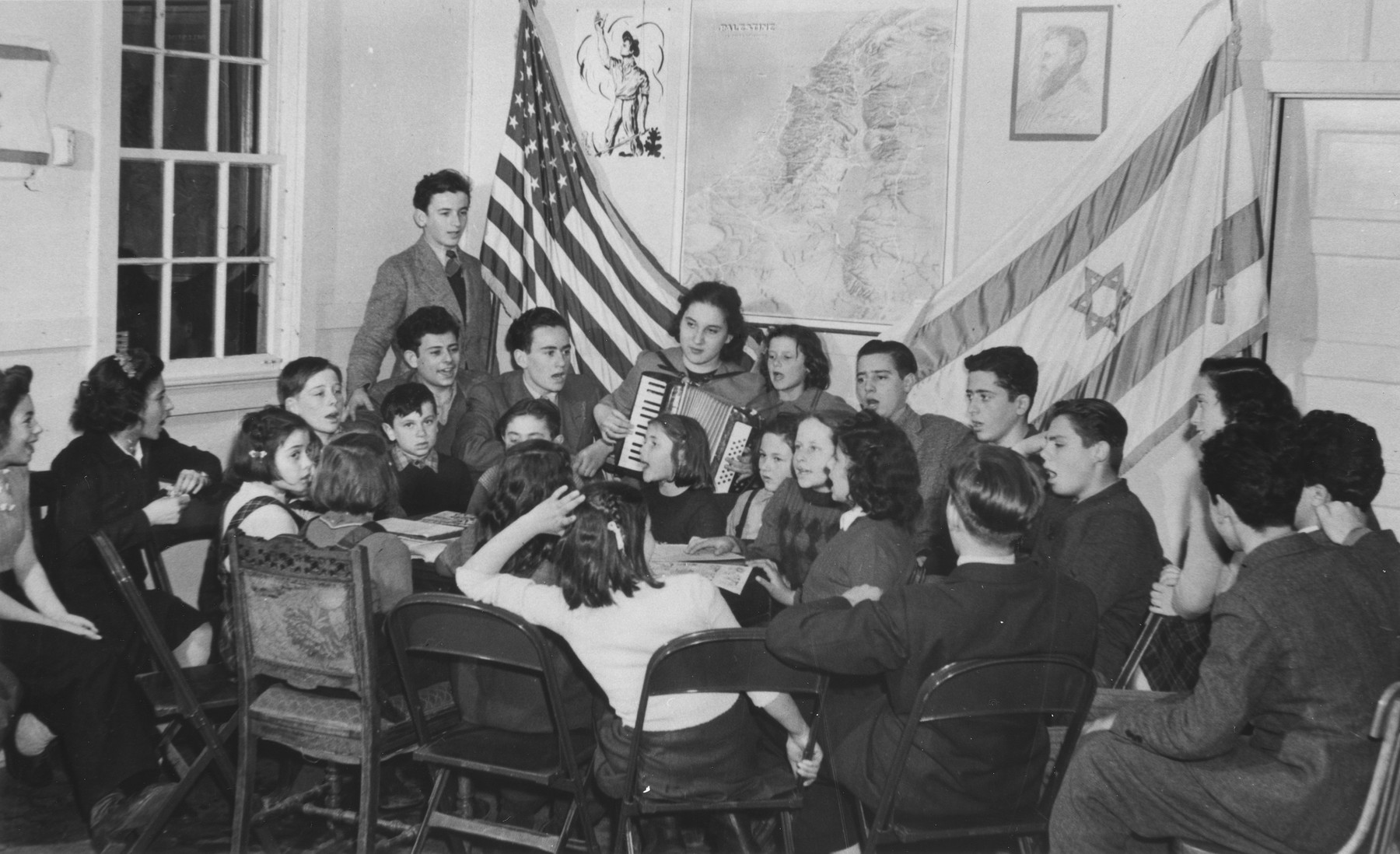 Jewish youth living at the Fort Ontario refugee shelter sing songs accompanied by an accordionist.   Those pictured include Elfi Strauber, Liesel Bader, Ruth Hendel, Walter Arnstein, Ernest Spitzer, Leo Levic, Wilko Kremer, David Hendel, Henny Notowitz, Adam Munz, Fortunee Levic, Paul Bokros, Ivo Lederer, Paul Arnstein, Neli Bokros, Herman Kremer, and Joseph Bernard Hirt, standing on the far left next to the American flag.  The pen and ink drawing on the wall was drawn by Adam Munz.