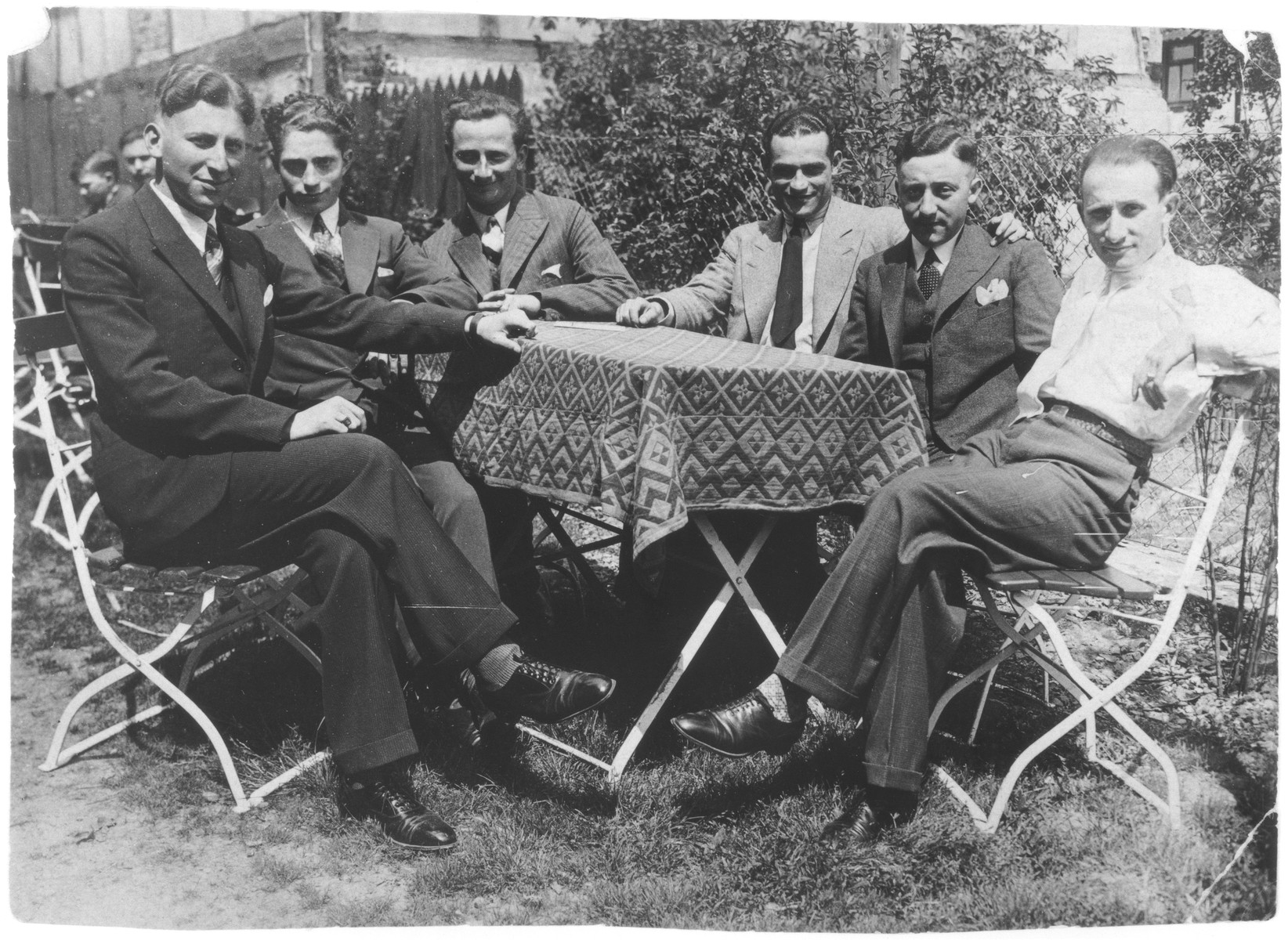 A group of young Jewish men wearing suits and ties sits outside around a table.  Among those pictured is Siegfried Kaiser.