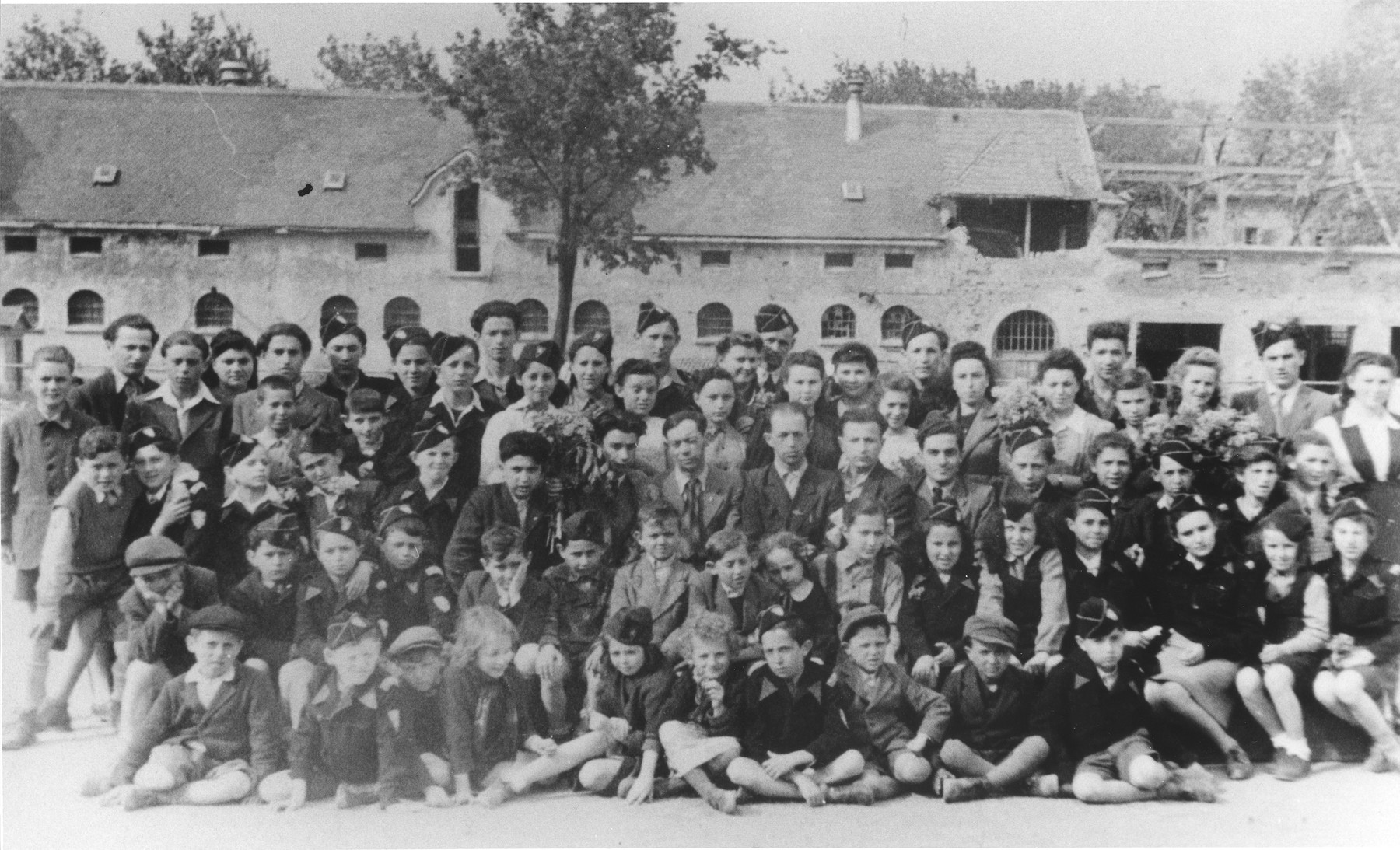 Group portrait of students in the Ulm displaced persons camp in front of their new school that is under construction.  Among those pictured are Regina Yablonska, Ida Wullach, Lila Rajs and Ruzia Rosen.